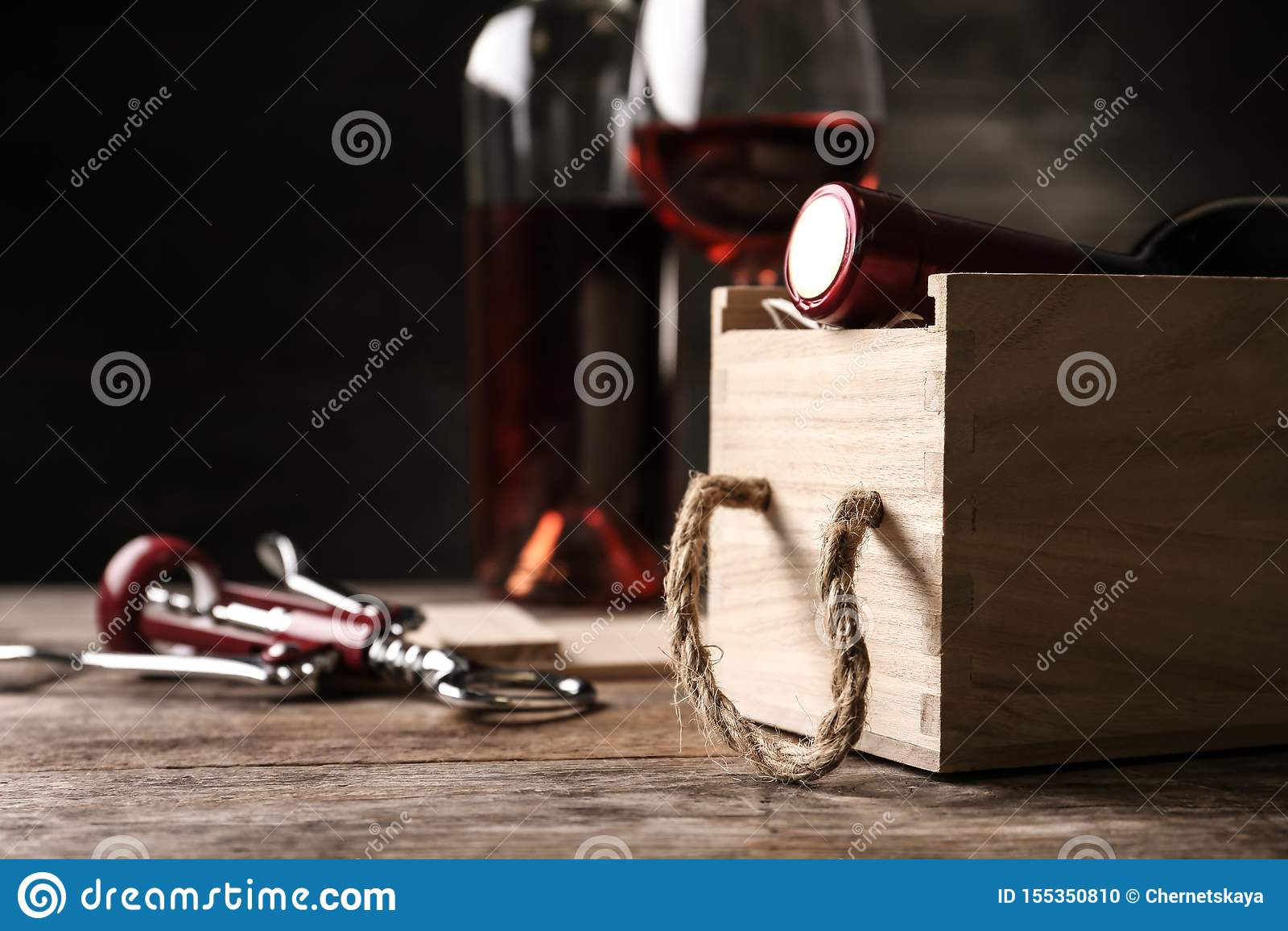 Cassa di legno aperta con la bottiglia di vino e della cavaturaccioli sulla tavola
