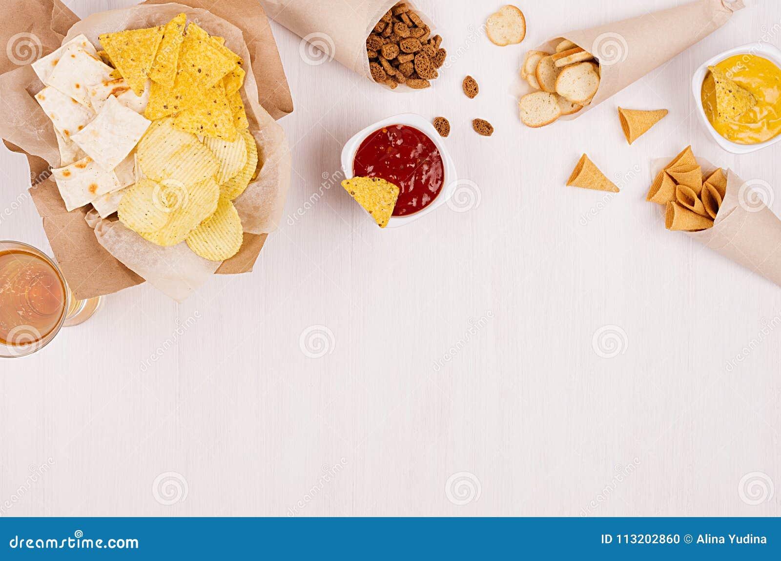 Casse-croûte d or croustillants sur la sauce à papier de métier, à nachos de triangles, blonde à bière, rouge et jaune dans la cu