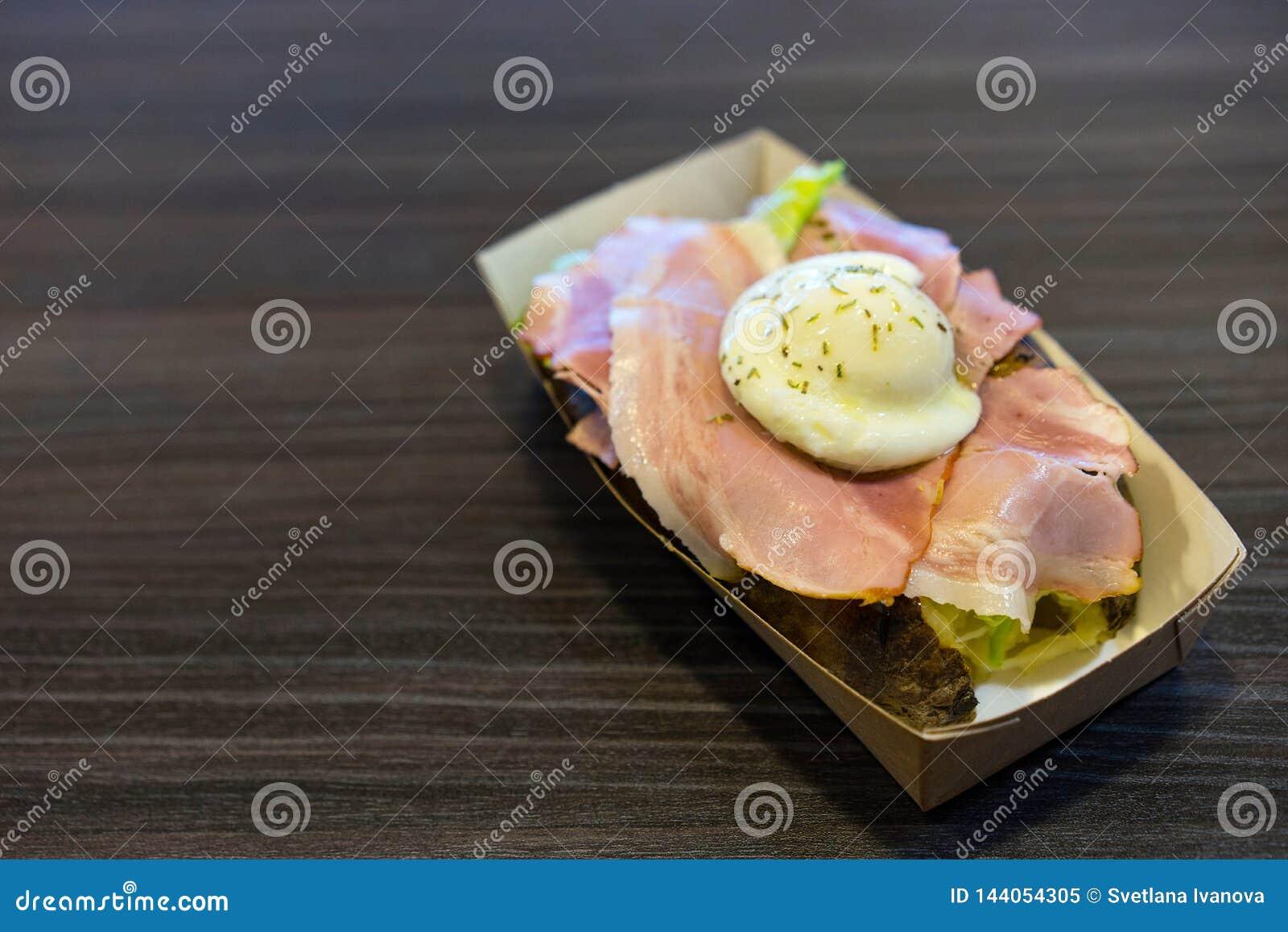 Casse-croûte des pommes de terre cuites au four, du lard et des oeufs pochés dans une boîte de carton sur une table noire