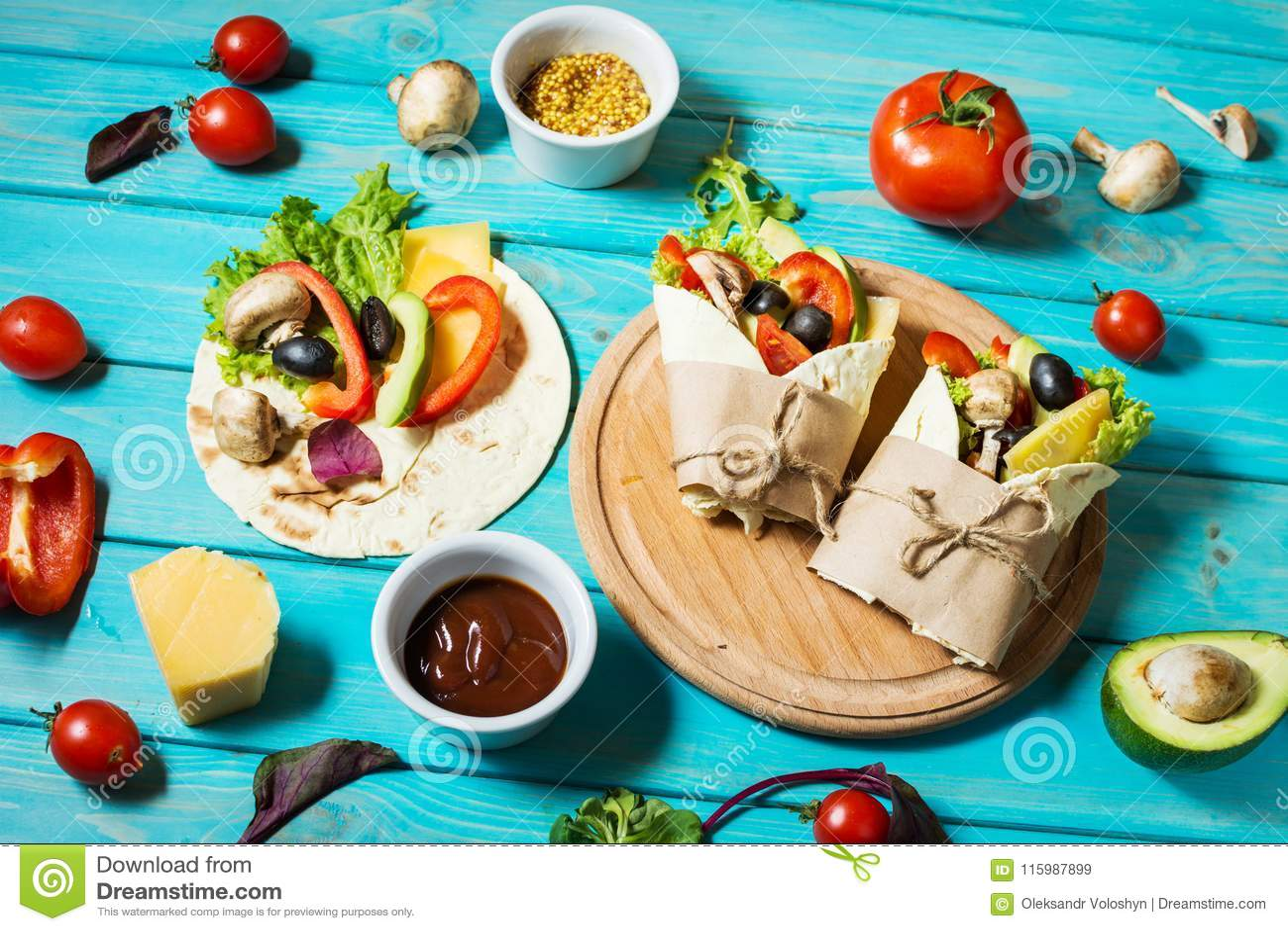 Casse-croûte sain de déjeuner de vegan Enveloppes de tortilla avec des champignons, des légumes frais et des ingrédients sur le f