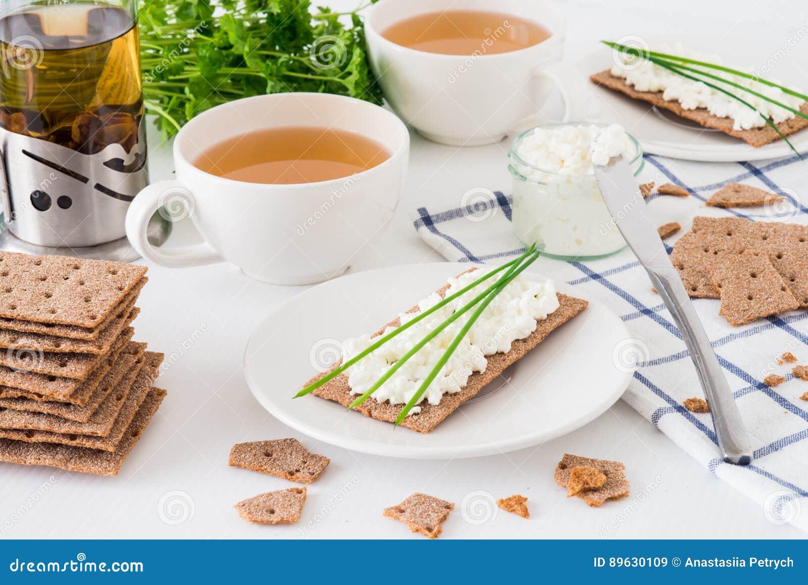 Casse-croûte avec les biscuits suédois frais de pain croustillant de thé et de seigle avec le fromage blanc, décoré à l oignon ve