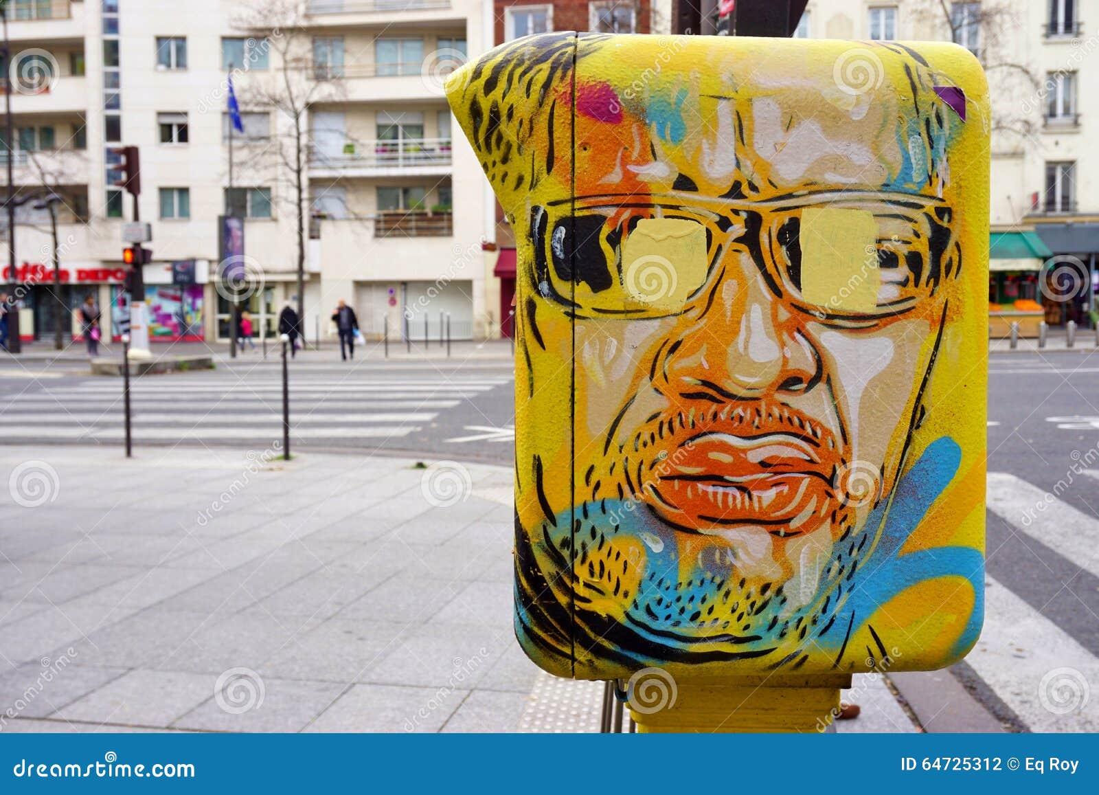 Cassetta delle lettere gialla dipinta coperta di arte della via dal muralista francese C215 dei graffiti a Parigi