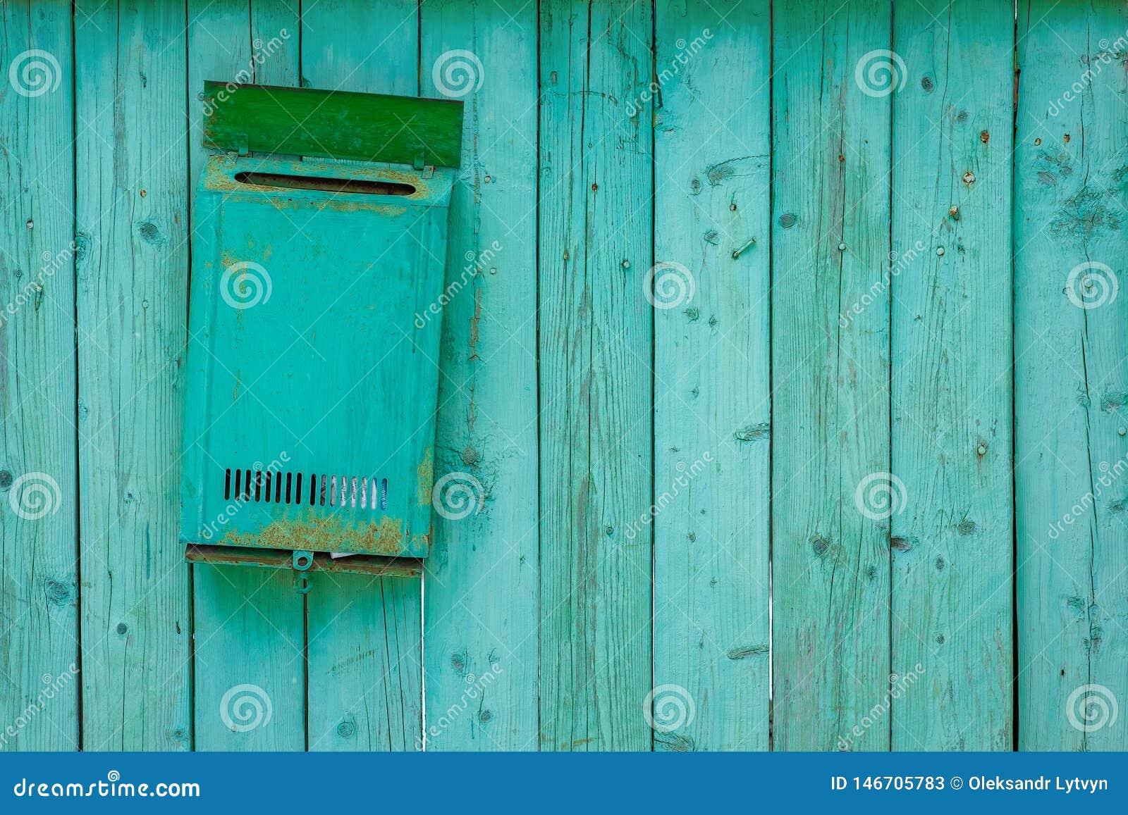 Cassetta delle lettere verde su un recinto di legno di legno