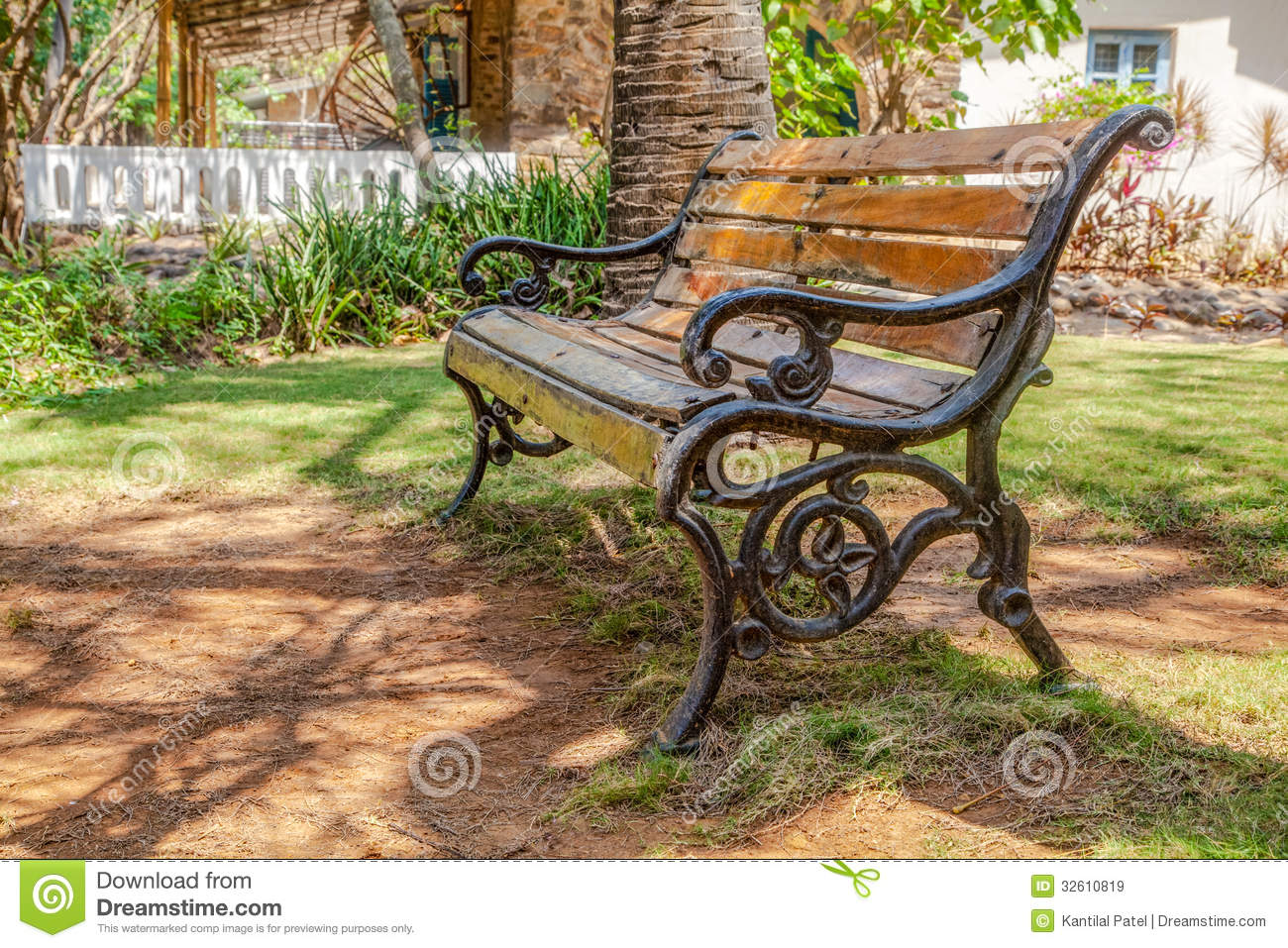 Horizontal color landscape of a wooden slat cast iron frame park bench ...
