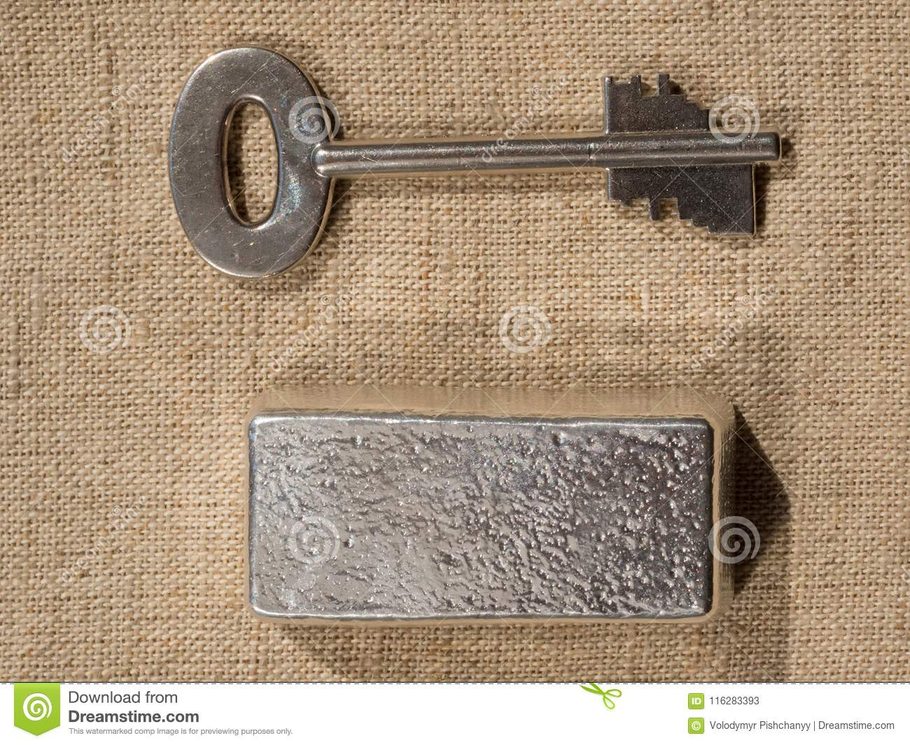 Cast silver bars and the key to the safe against a rough texture of the fabric