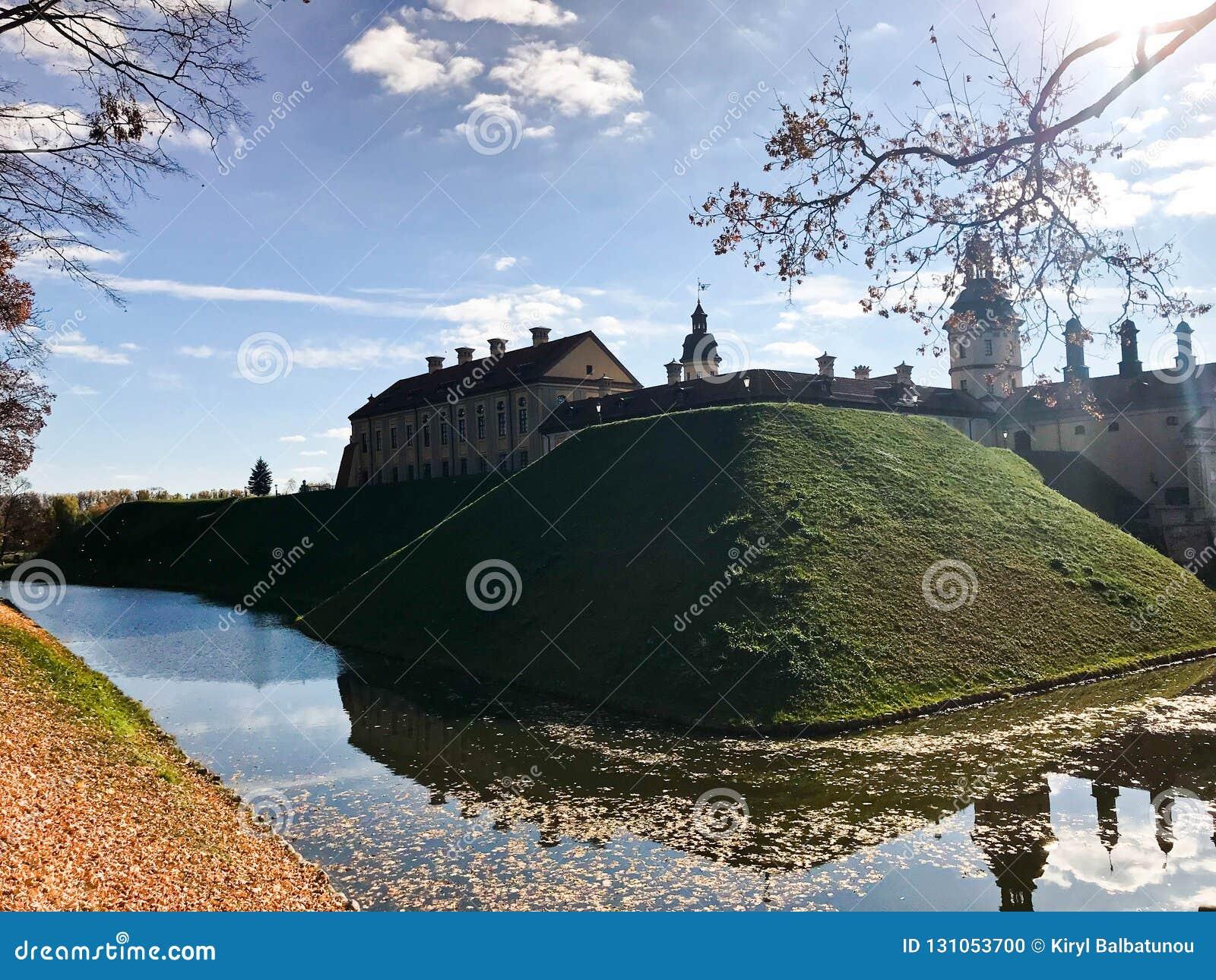 Castillo medieval viejo, antiguo con spiers y torres, paredes de la piedra y ladrillo rodeado por una fosa protectora con el wate