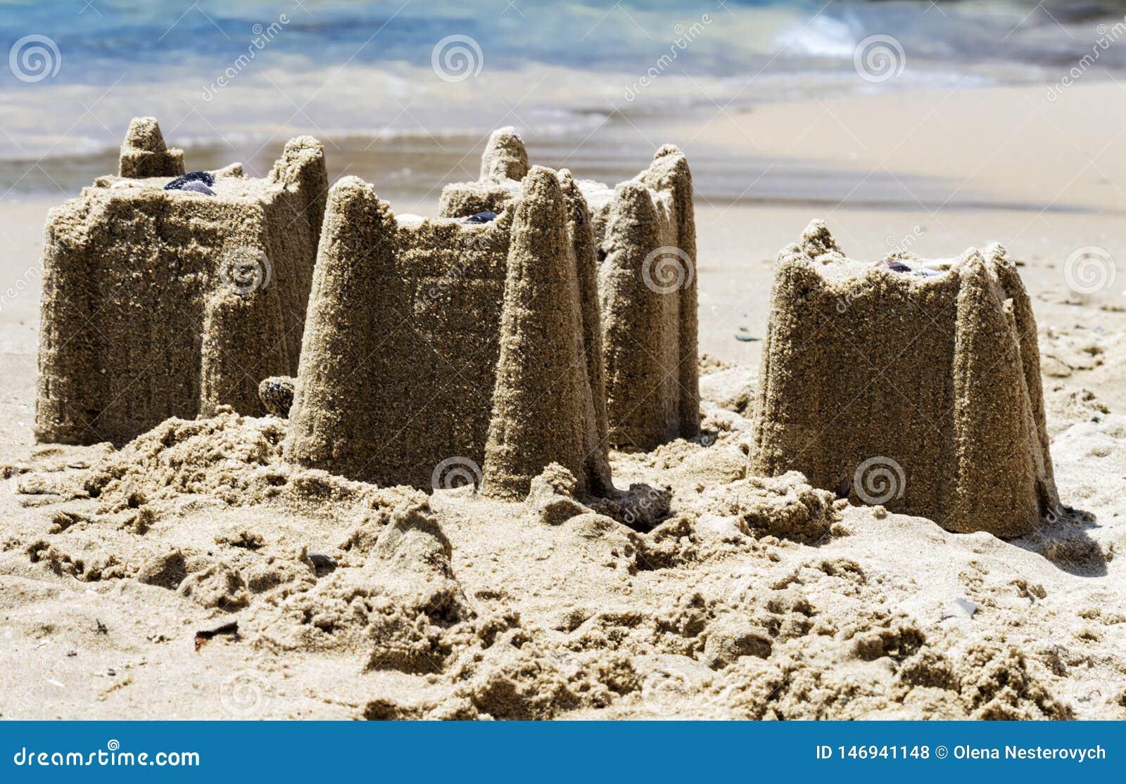 Castillos de arena en la playa, concepto de las vacaciones, entonado