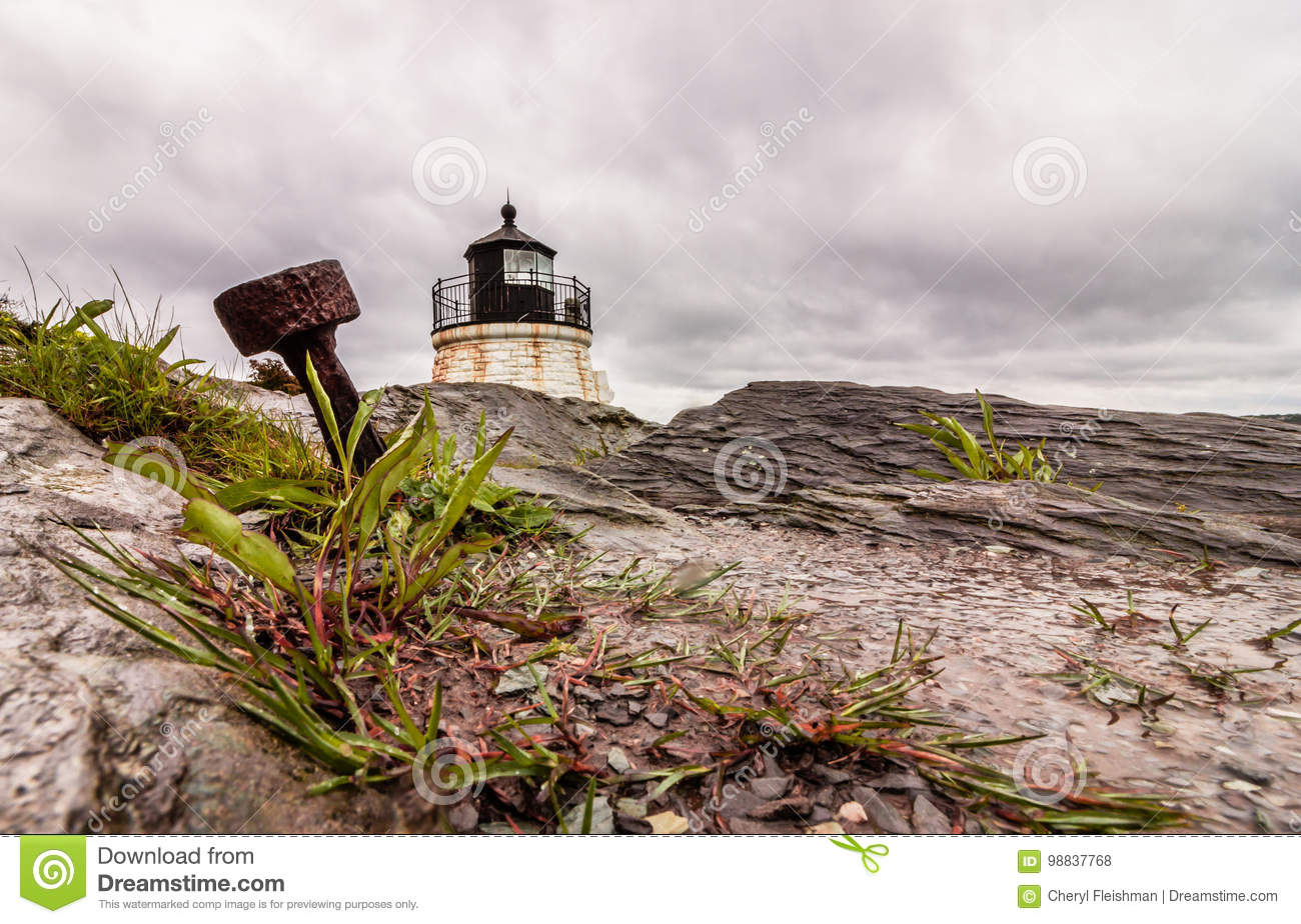 An anchor stands out in the dramatic rocky coastline at Castle Hill Lighthouse in Newport, Rhode Island, under a stormy sky