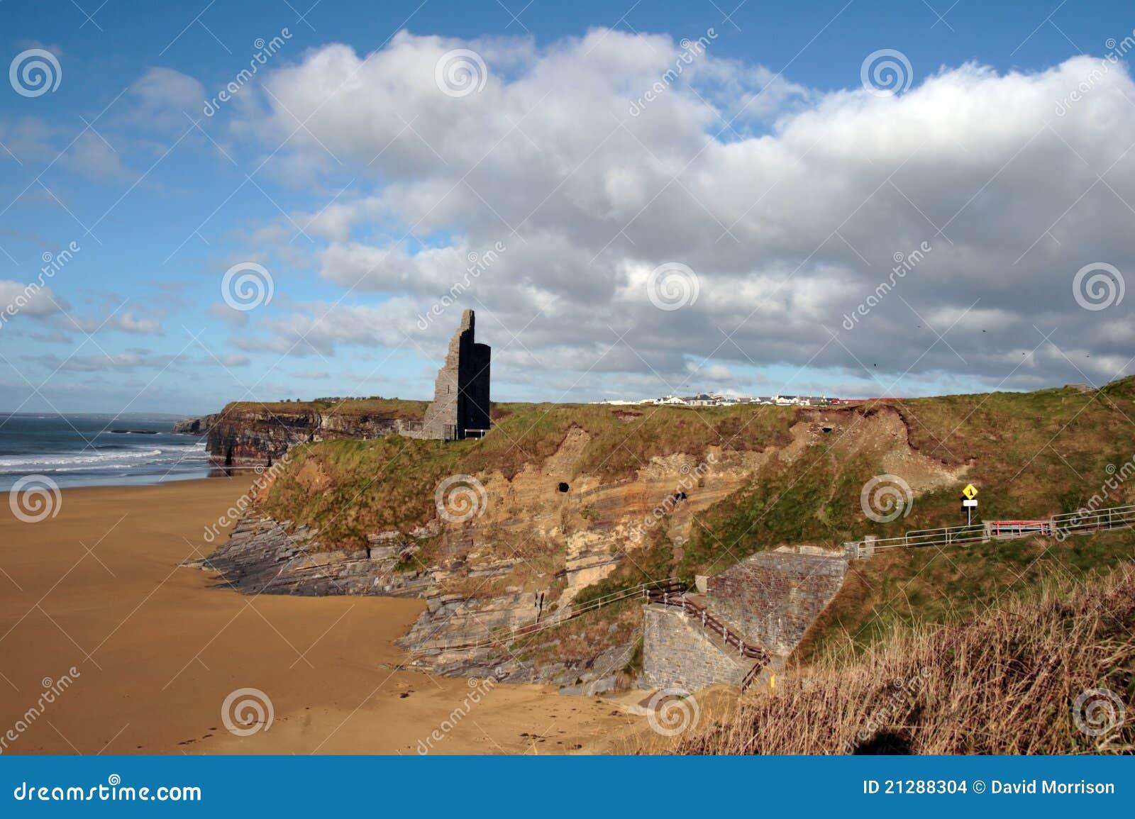 Castle ruins on cliffs above beach