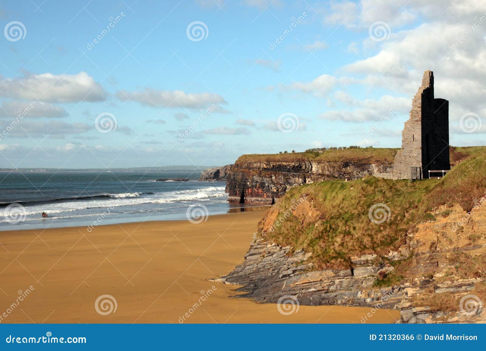 Castle ruins on cliffs above beautiful beach