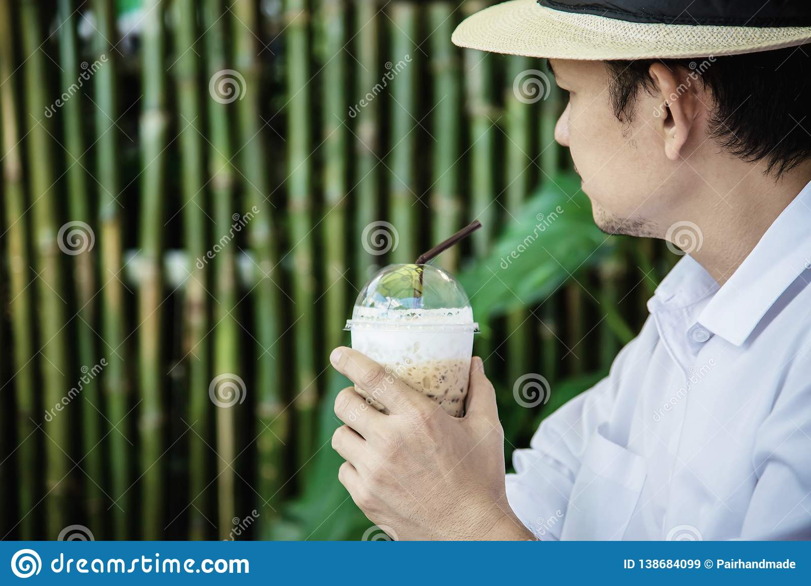 Casual Asian man drink ice coffee happily in nature