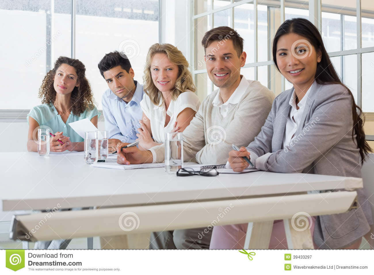 Casual Business Team Smiling At Camera During Meeting Stock Photo