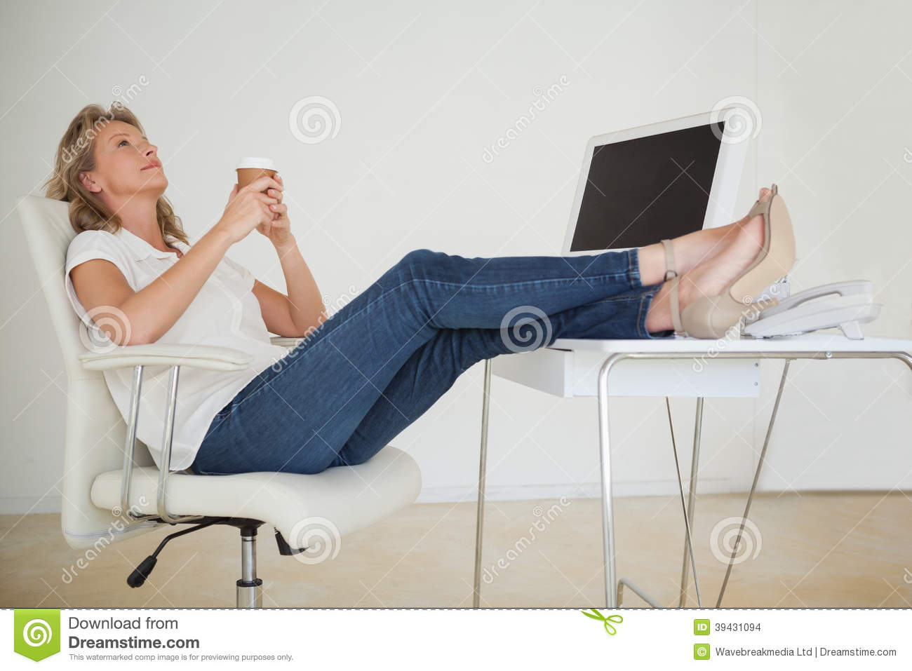Casual Businesswoman Having A Coffee With Her Feet Up At