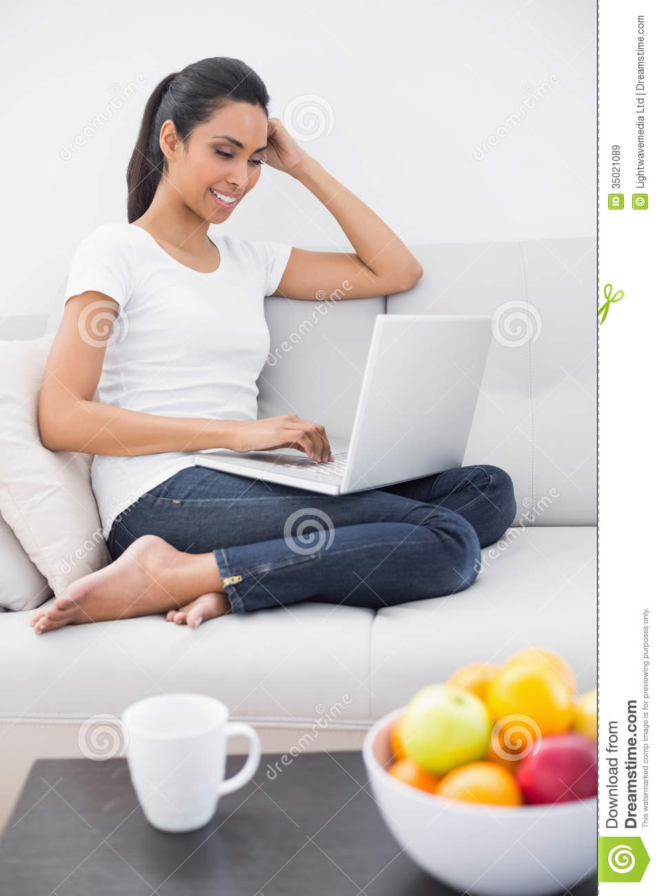 casual happy woman using her notebook sitting on couch. Black Bedroom Furniture Sets. Home Design Ideas