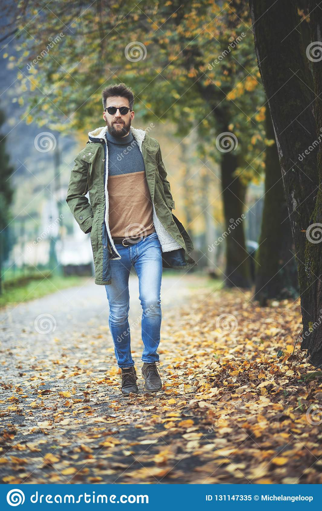 Casual hippie style man walking among autumn leaves