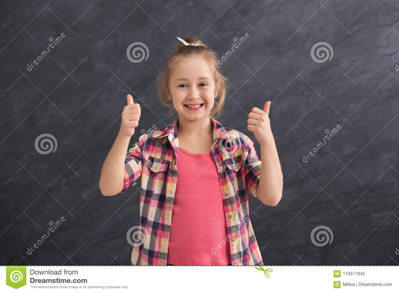 Casual little girl showing thumbs up at gray background
