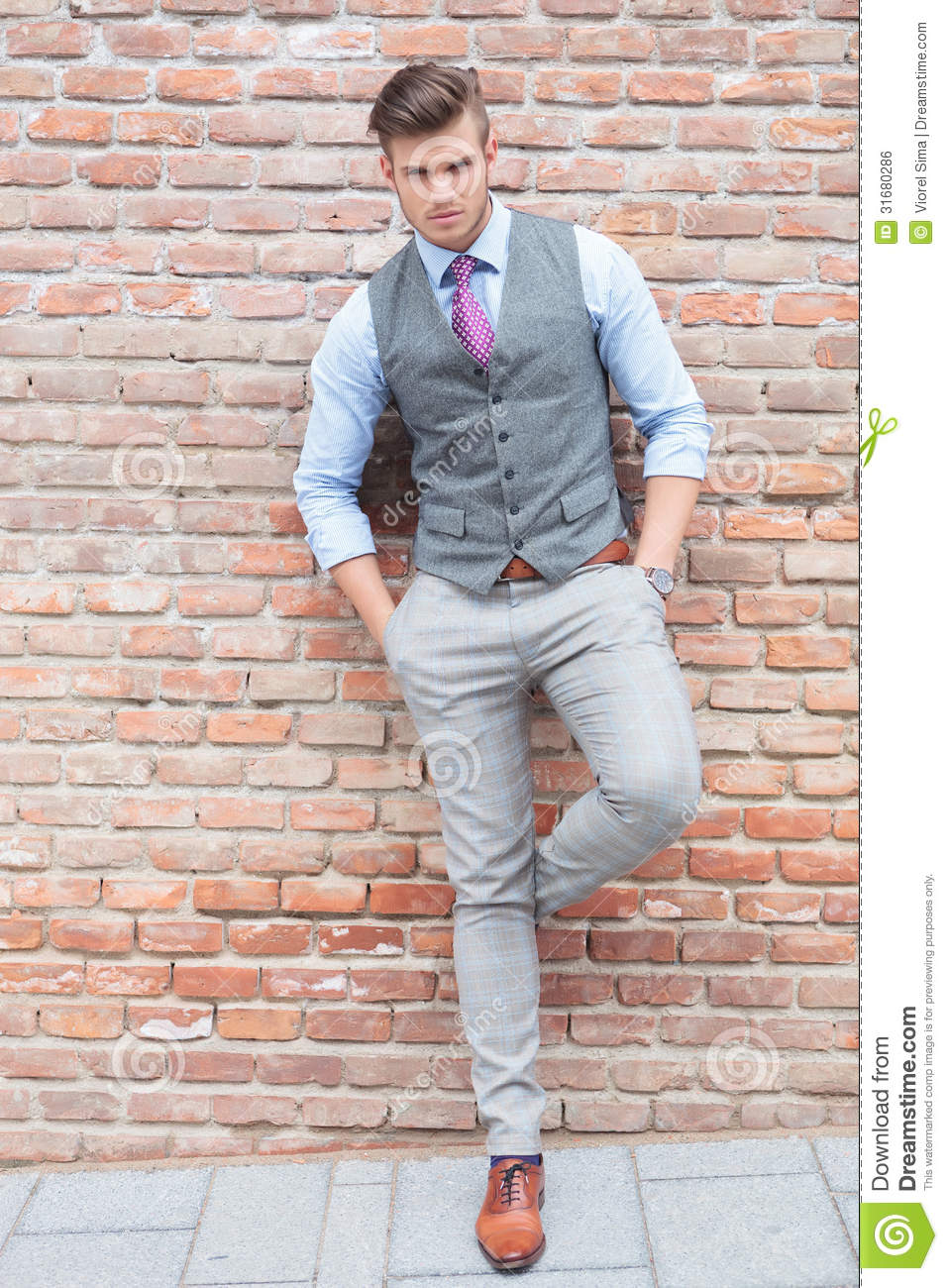 Casual Man Leans On Wall And Looks At Camera Stock Photo ...