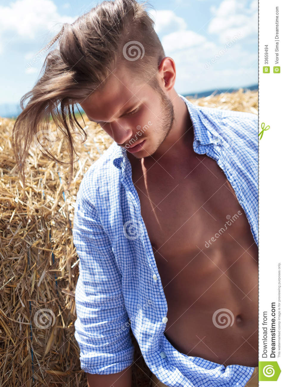 casual man with long hair looks down outdoor stock images