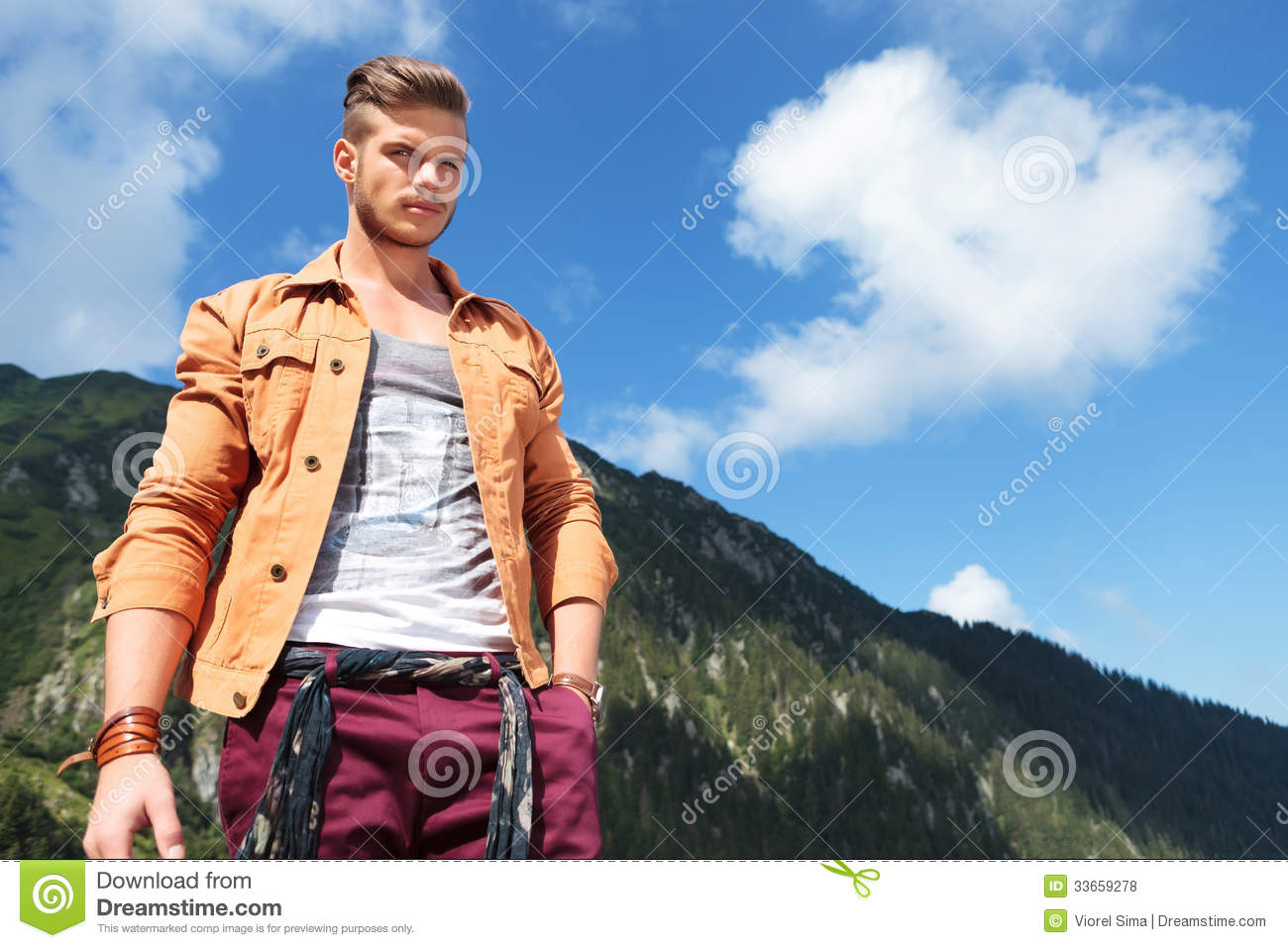 Casual man looks down at camera in mountains