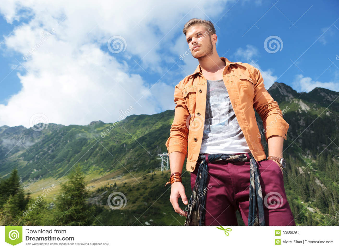 Casual man in mountains holds a hand in pocket and looks away