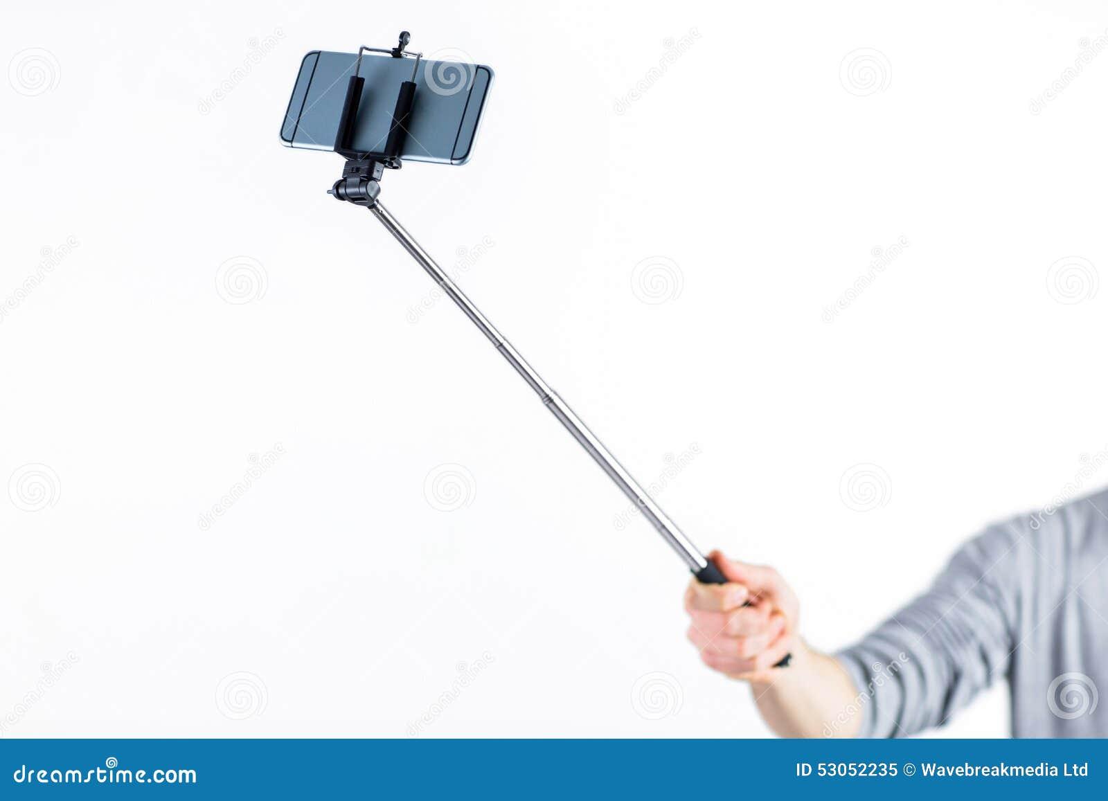 casual man using a selfie stick stock photo image 53052235. Black Bedroom Furniture Sets. Home Design Ideas