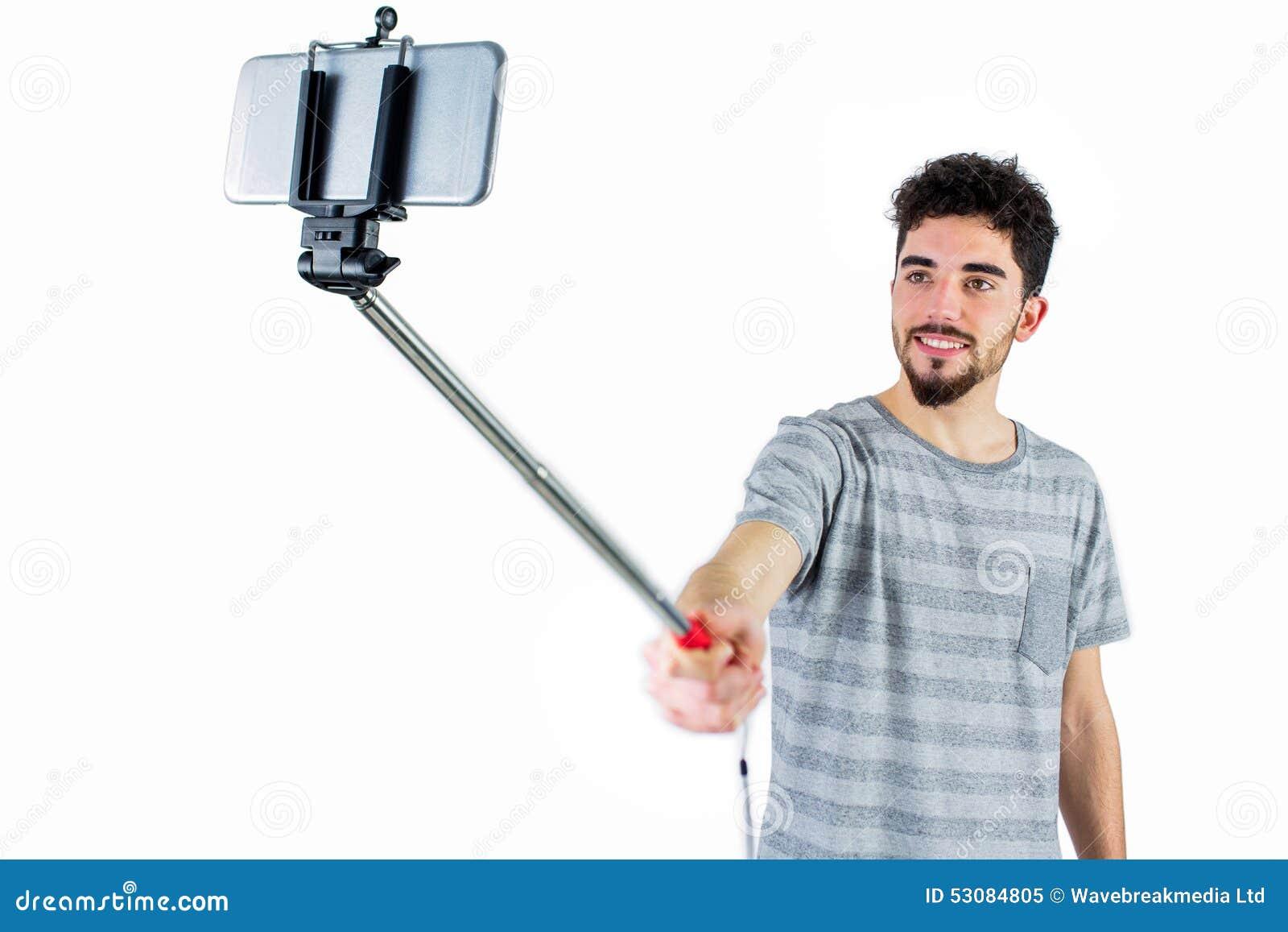 casual man using a selfie stick stock photo image 53084805. Black Bedroom Furniture Sets. Home Design Ideas