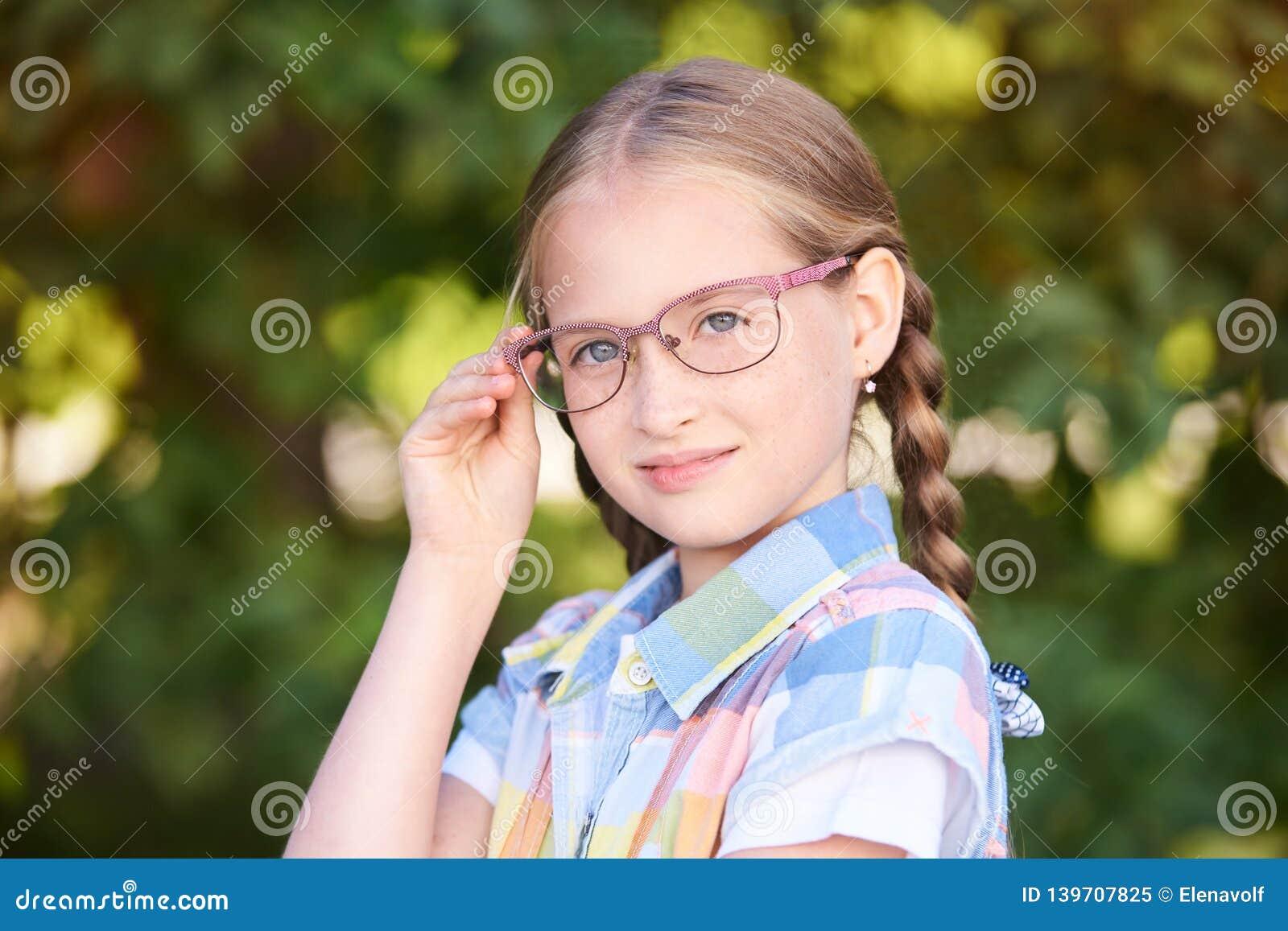 Casual schoolchildren. Little girl smile. Standind outdoor with eyeglasses. First grade