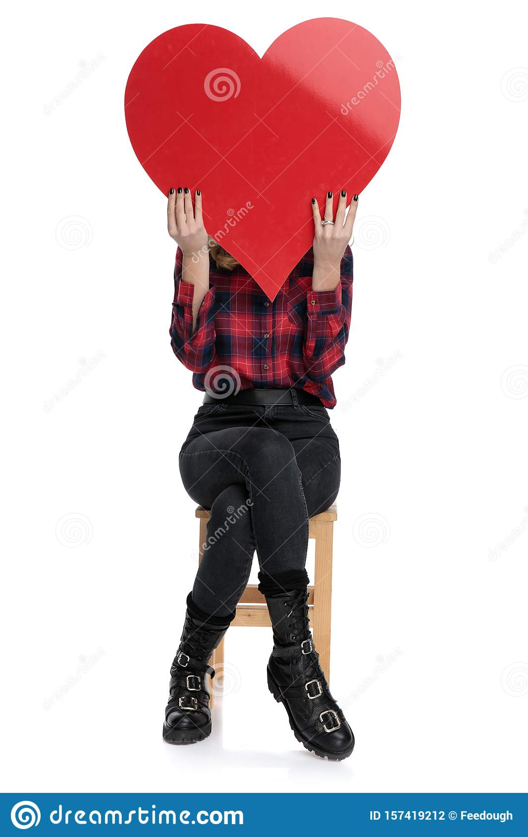 Casual woman sitting with face covered by a heart