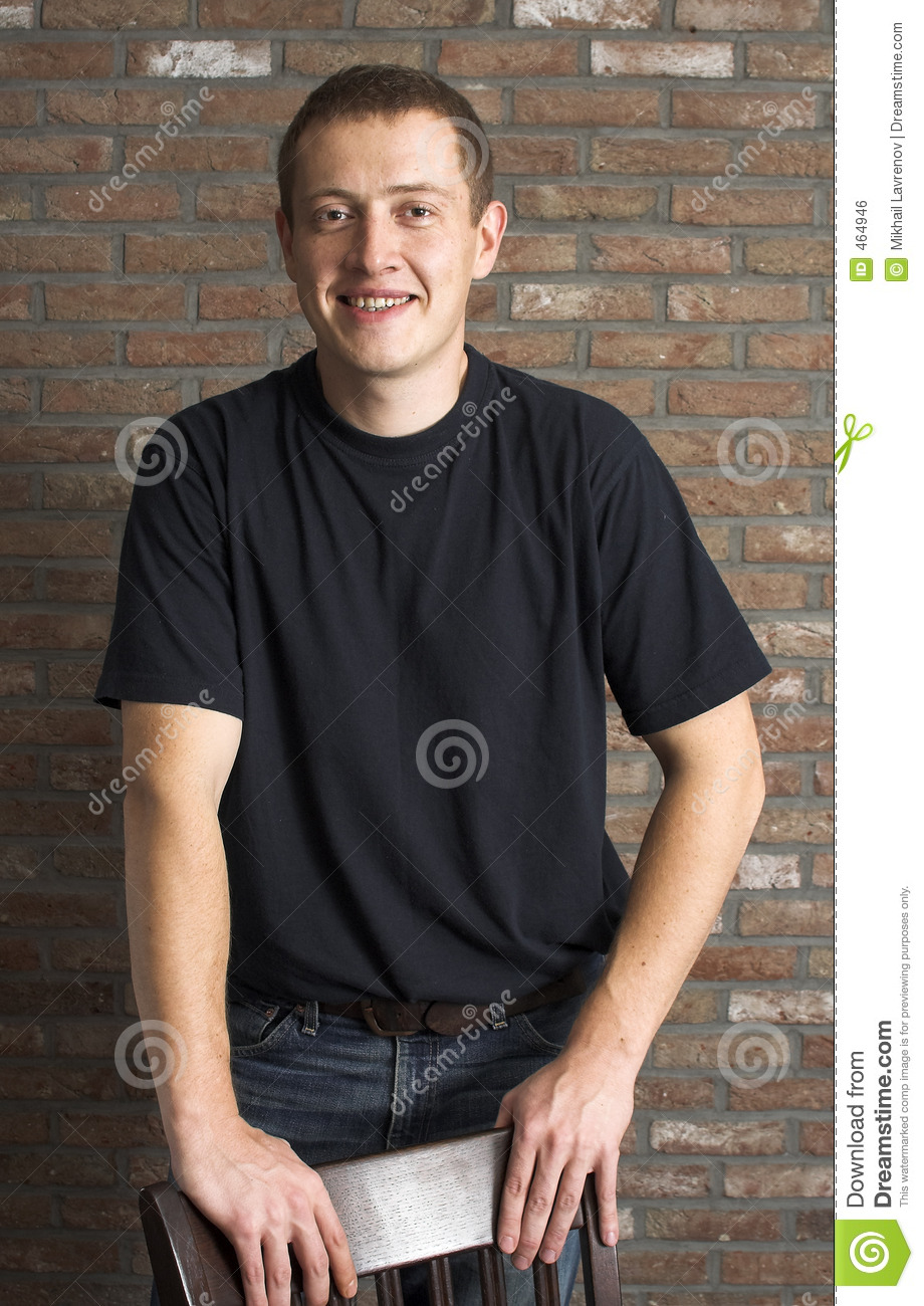Casual young adult man standing next to the brick wall