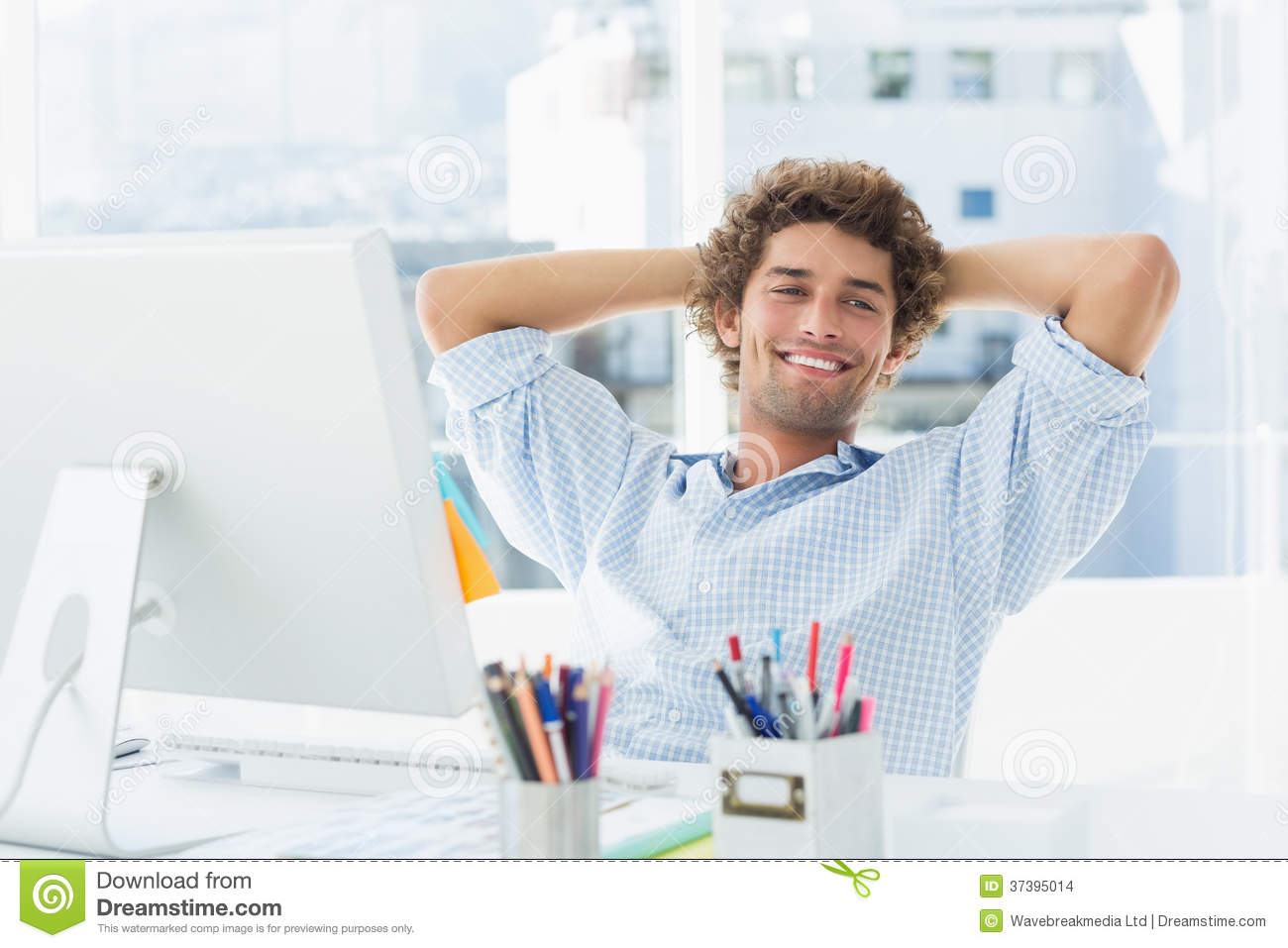 casual young man with computer in a bright office stock