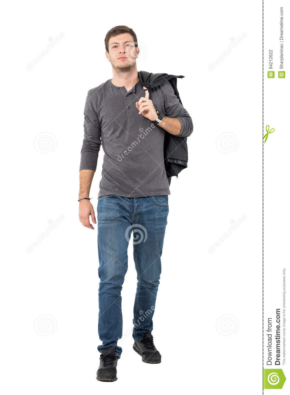 752b2c3bc0 Casual young man walking forward carrying jacket over shoulder looking at  camera. Full body length portrait isolated over white background.