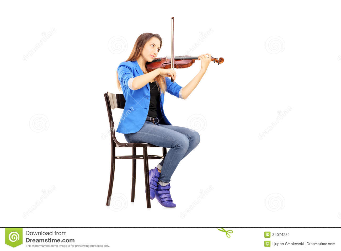 Casual Young Woman Seated On A Wooden Chair Playing The