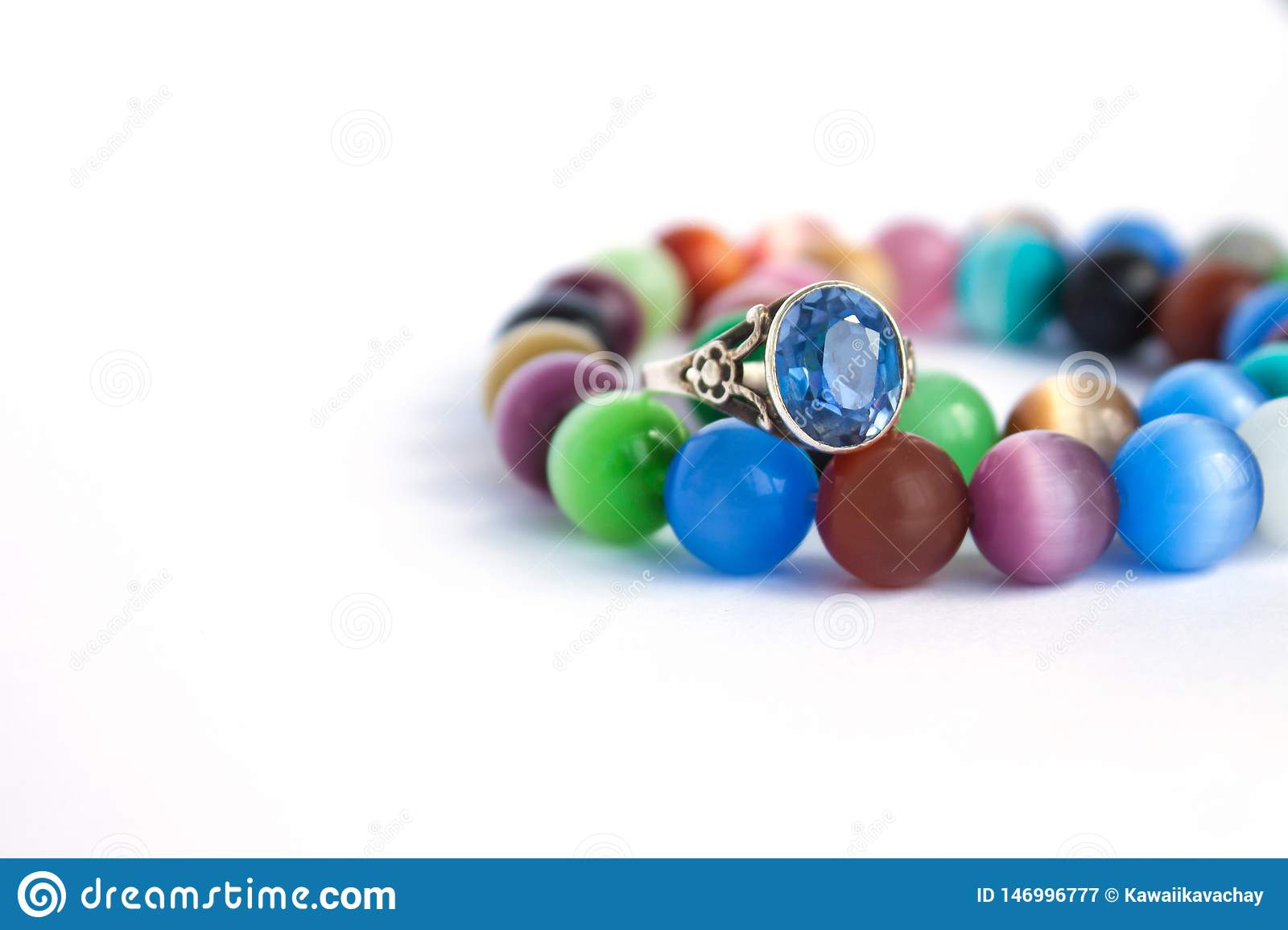 Cat`s eye quartz necklace and bracelet, selective focus on white background isolated. Colourful precious stones.