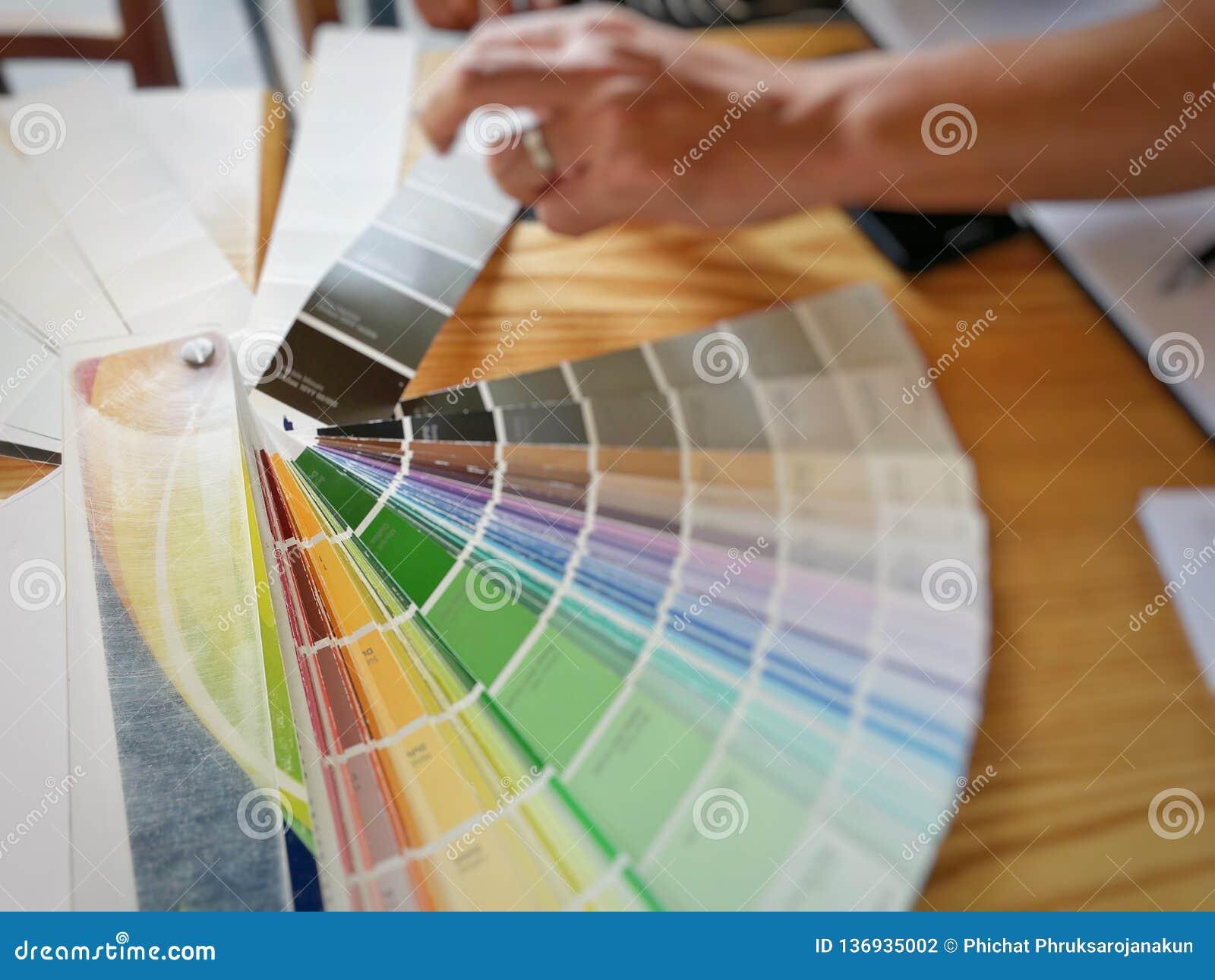 Catalogus van kleur met hand die van de mens voor binnenlands ontwerp selecteren