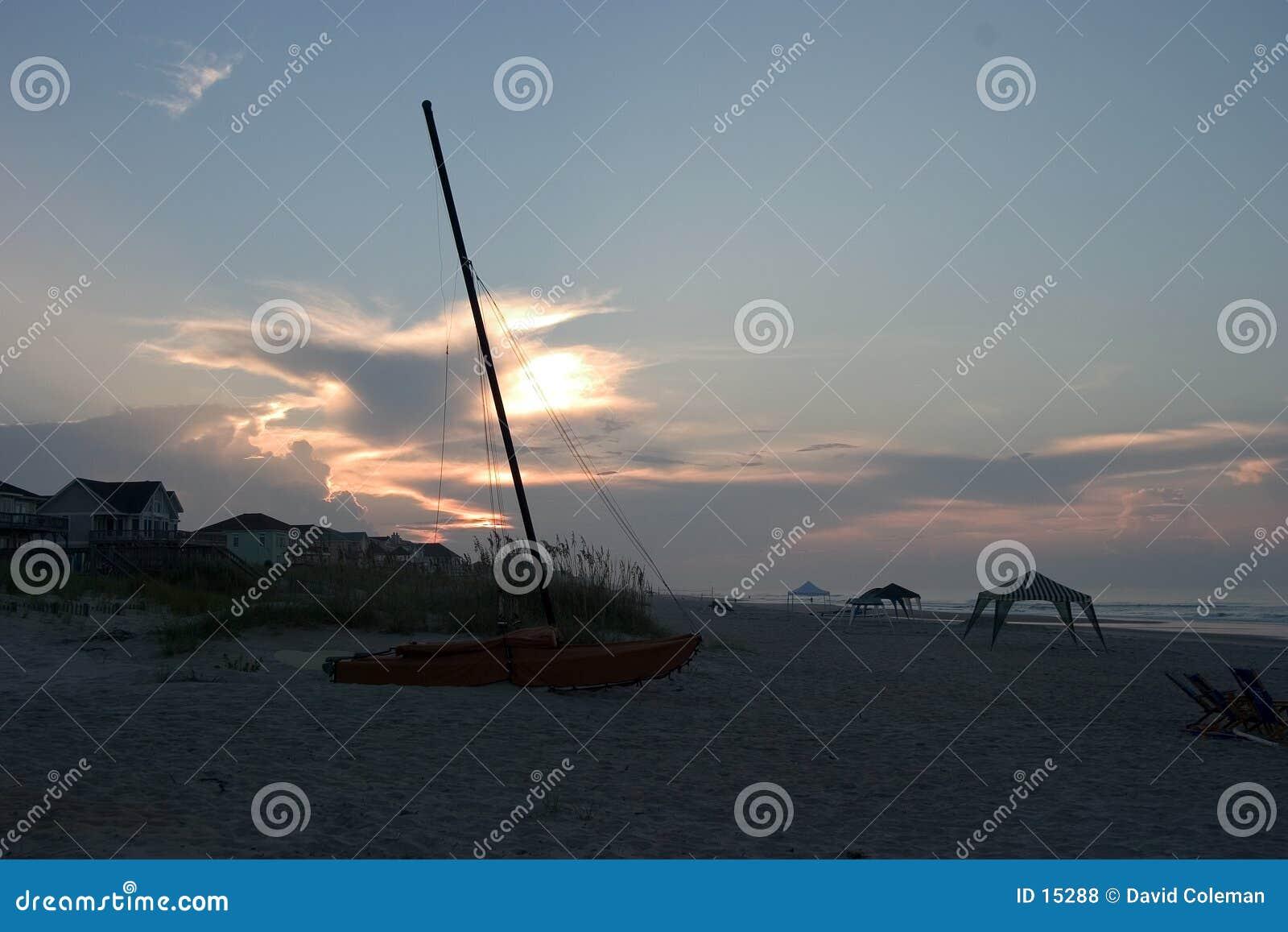 Catamarã na praia, nascer do sol