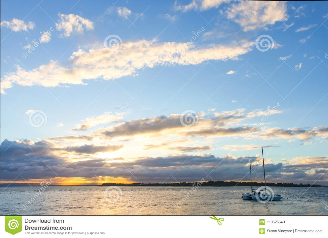 Catamaran sailboat in water at sunset with sun breaking though clouds on horizon