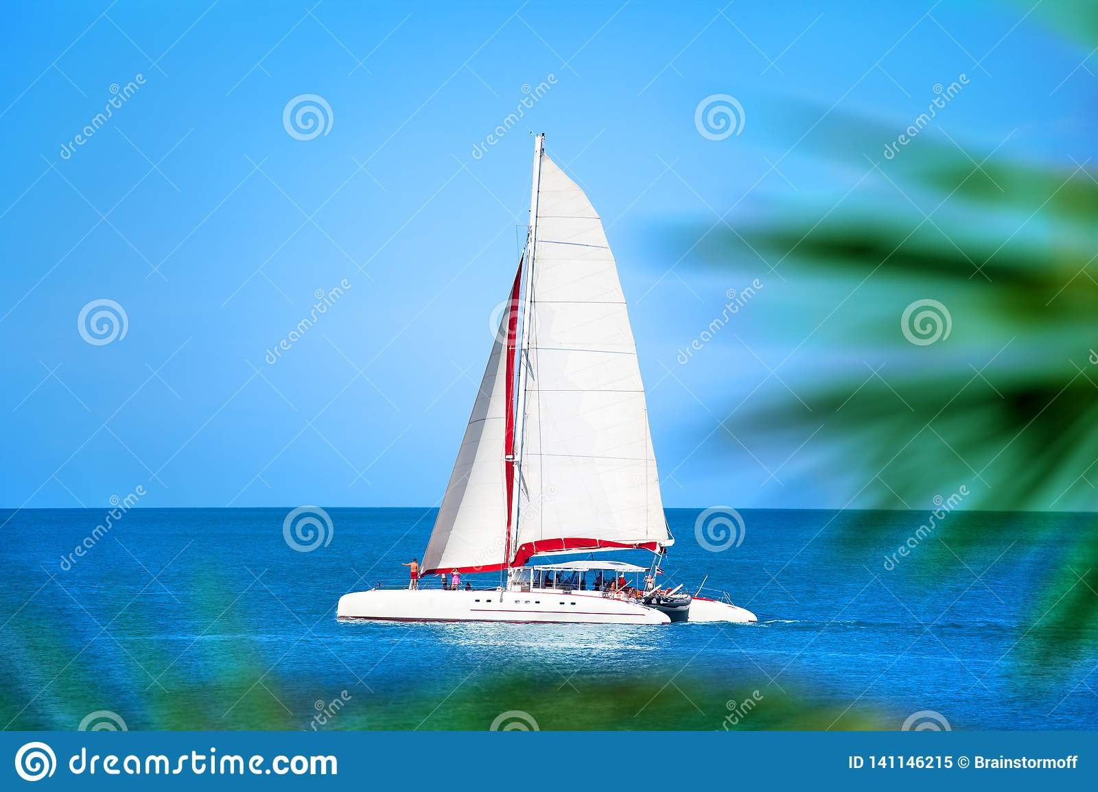 Catamaran with white sail in blue sea, palm branches background, people relax on boat, summer vacation sea trip on ship
