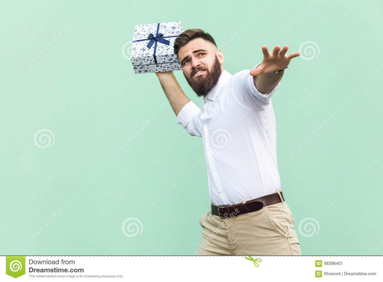 Catch your gift! Young adult man swung and wants to throw off your gift box, isolated on light green background.