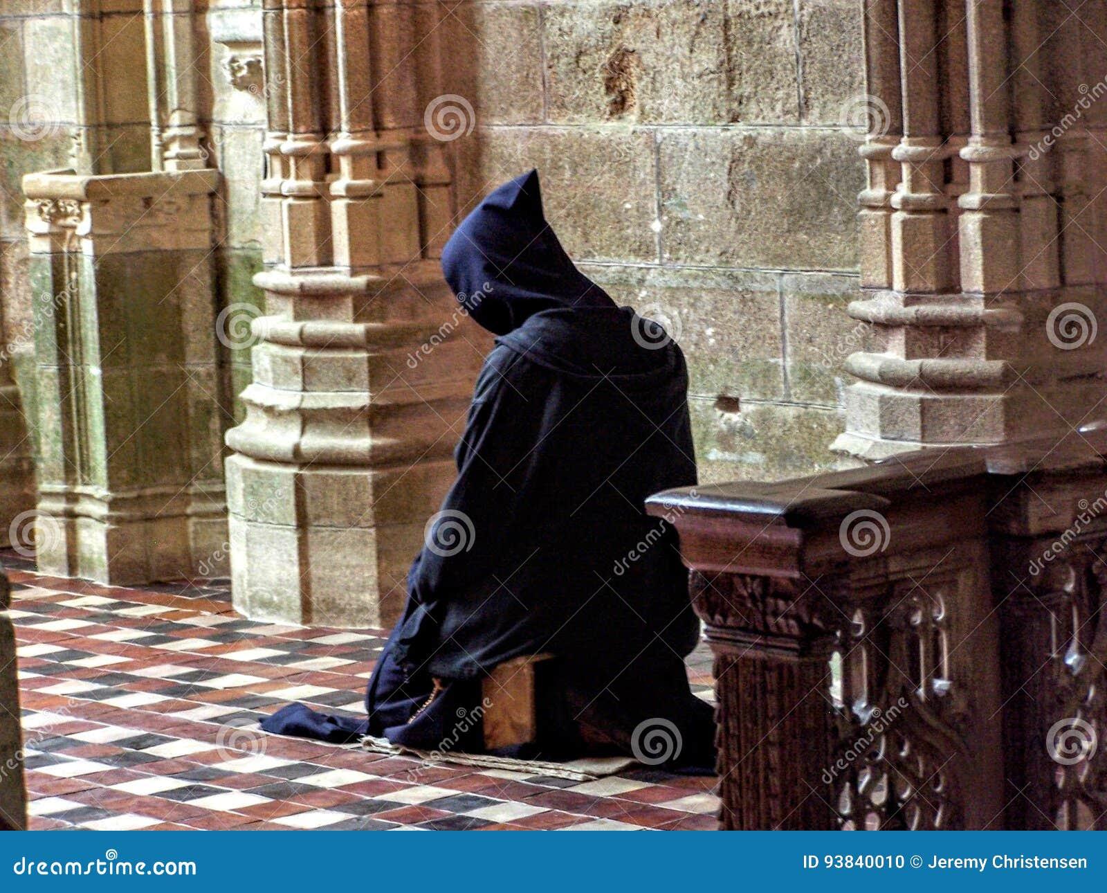 Catholic Christian Monk kneeling in humble prayer asking God for help