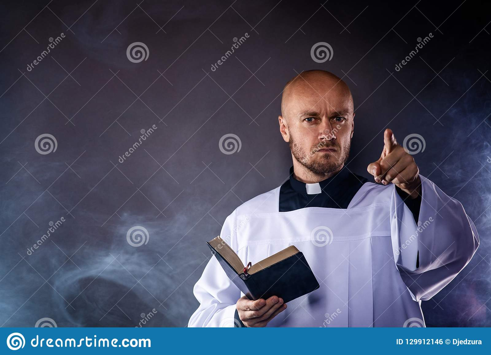 Catholic Priest In White Surplice And Black Shirt With Cleric Collar