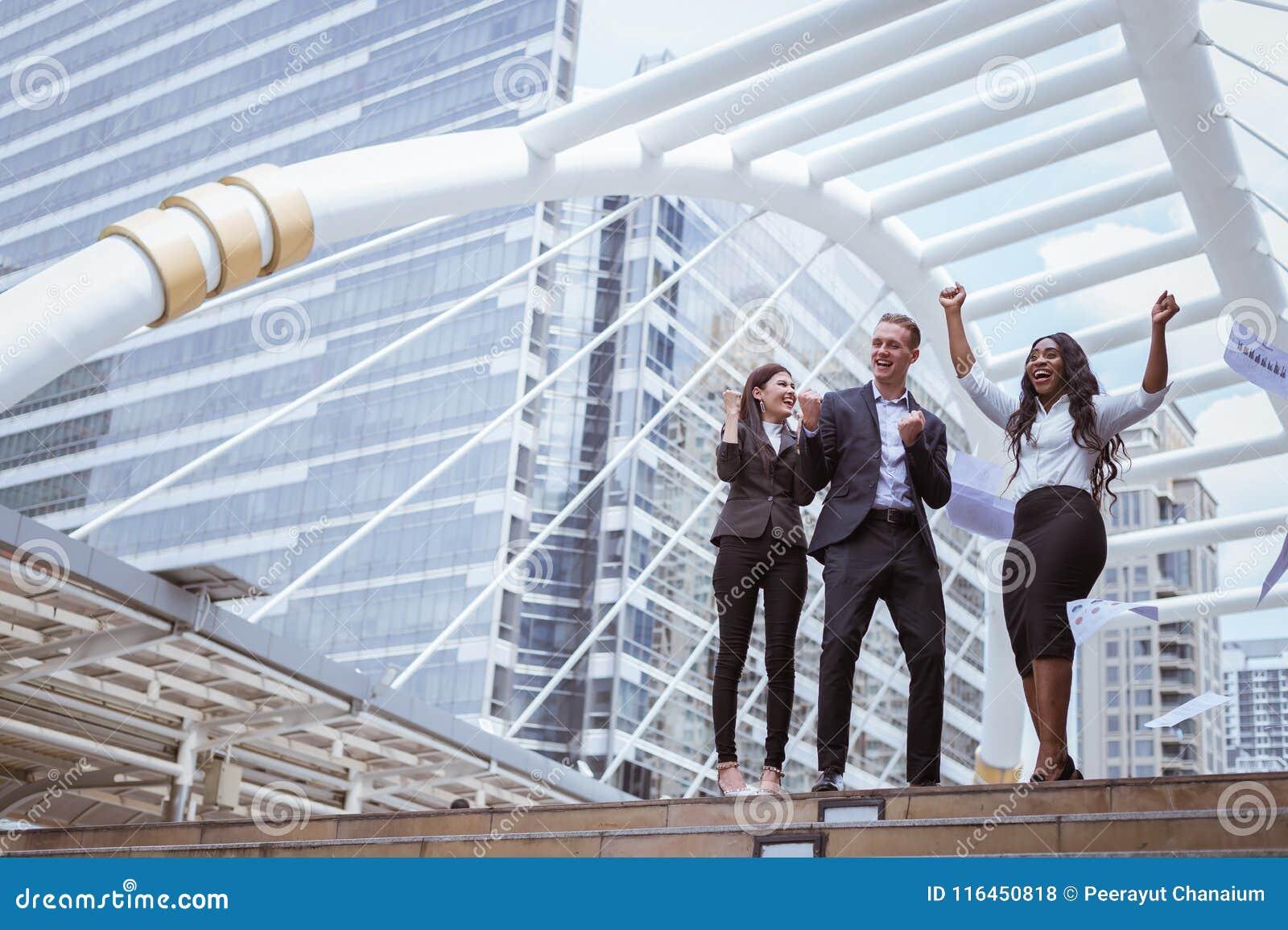 Caucasian affärsman, asiatisk affärskvinna och leende för svartaffärskvinna och lyfta upp två händer