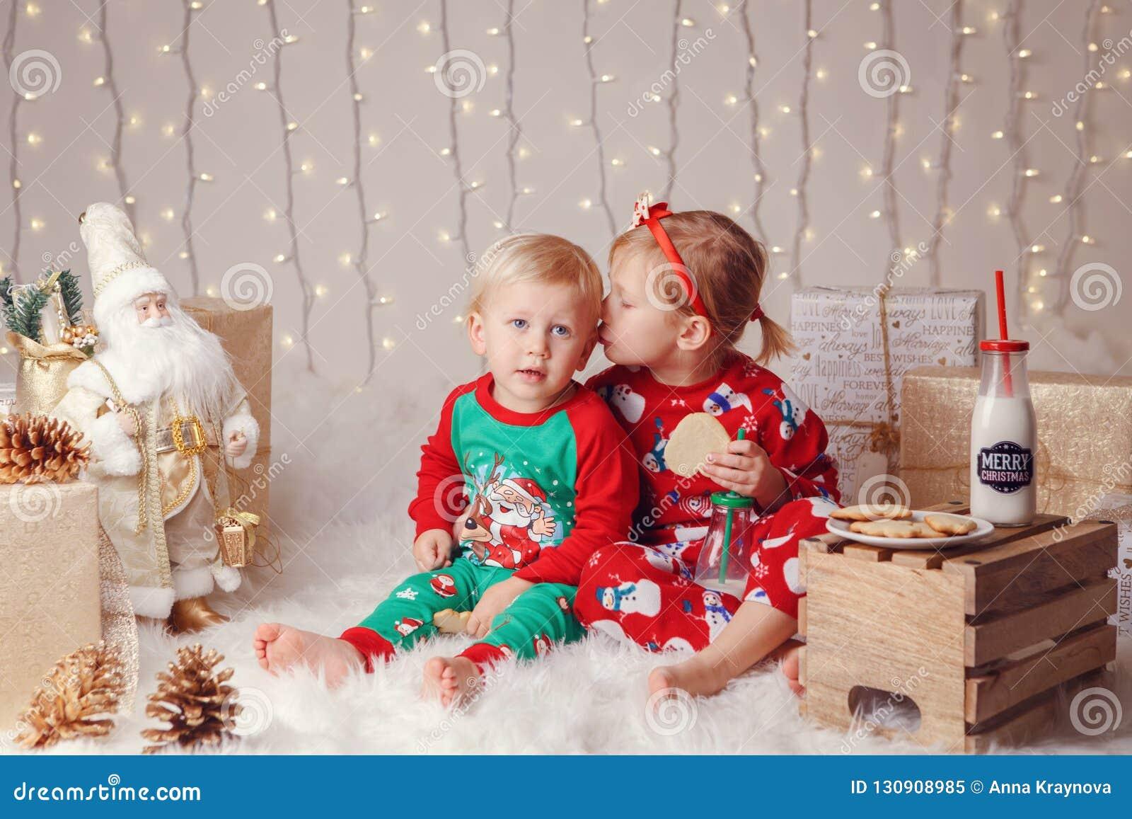 Caucasian barnsyskongrupp i tröjor som sitter tillsammans att krama fira jul eller nytt år