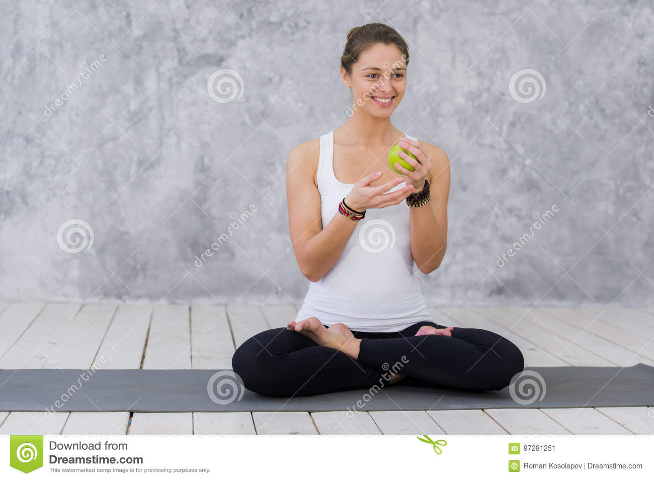 Caucasian beautiful healthy athletic sportive girl eat green apple after the training and looking at camera