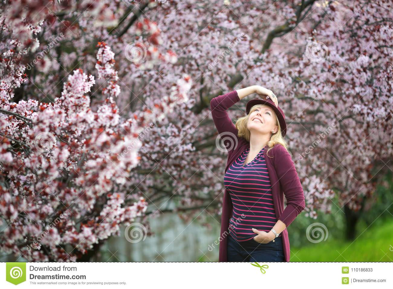 Caucasian blond woman with long hair in purple fedora hat near blossoming tree