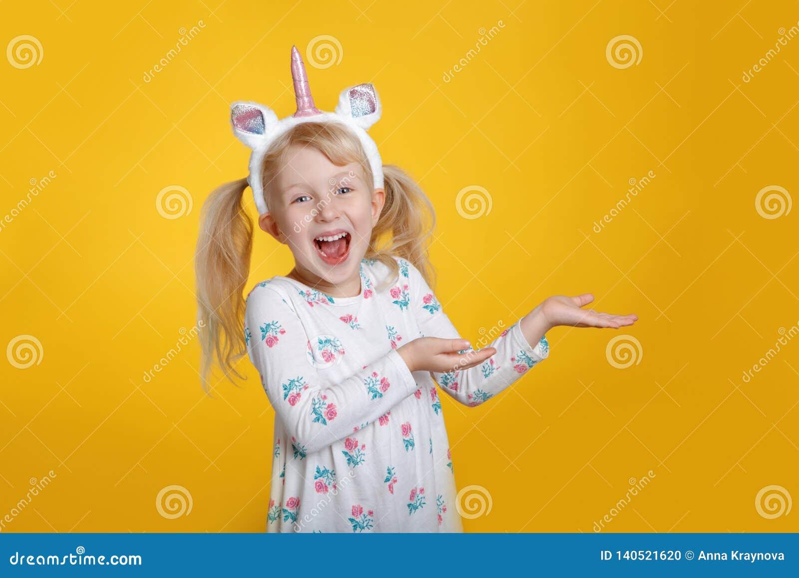 Caucasian blonde girl in white dress wearing unicorn headband horn and ears