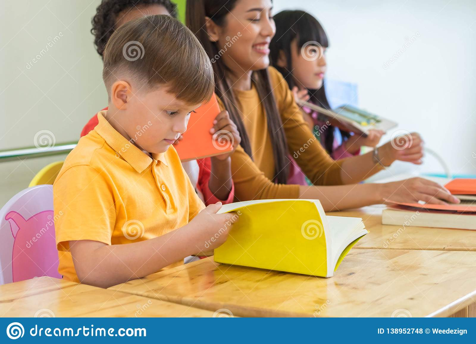 Caucasian boy ethnicity kid reading book white learning in classroom with friends and teacher in kindergarten school, education