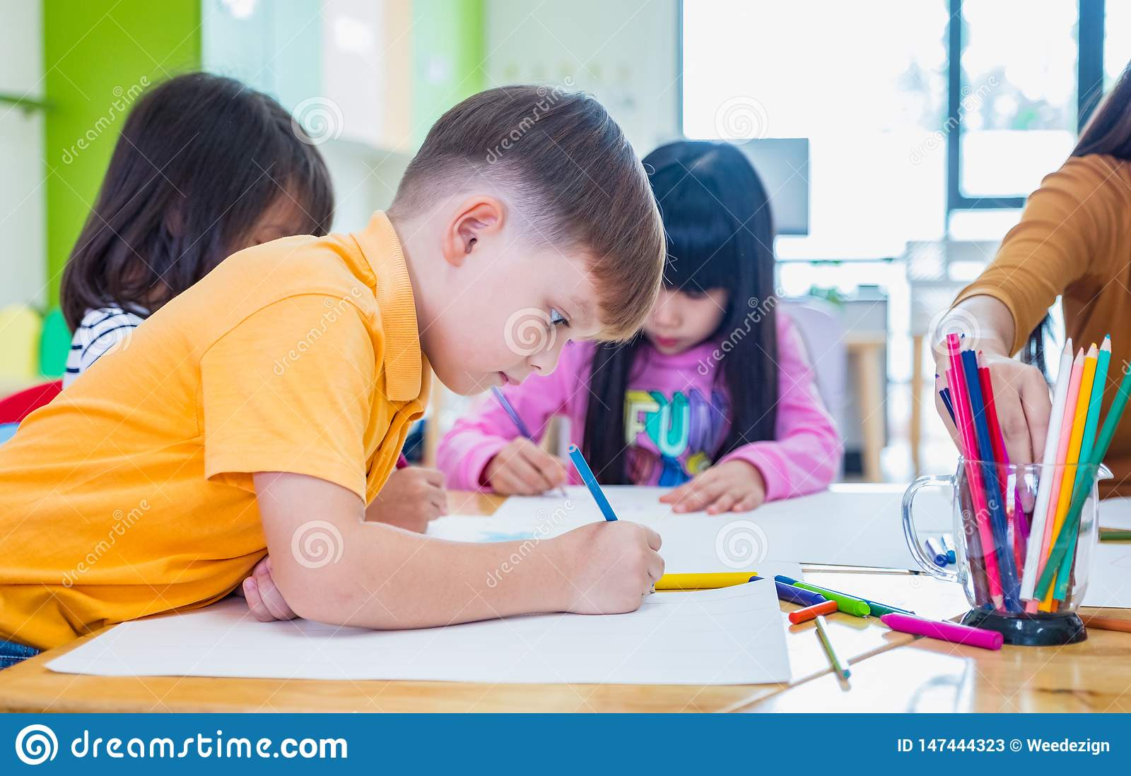 Caucasian boy ethnicity kid smiling white learning in classroom with friends and teacher  in kindergarten school, education