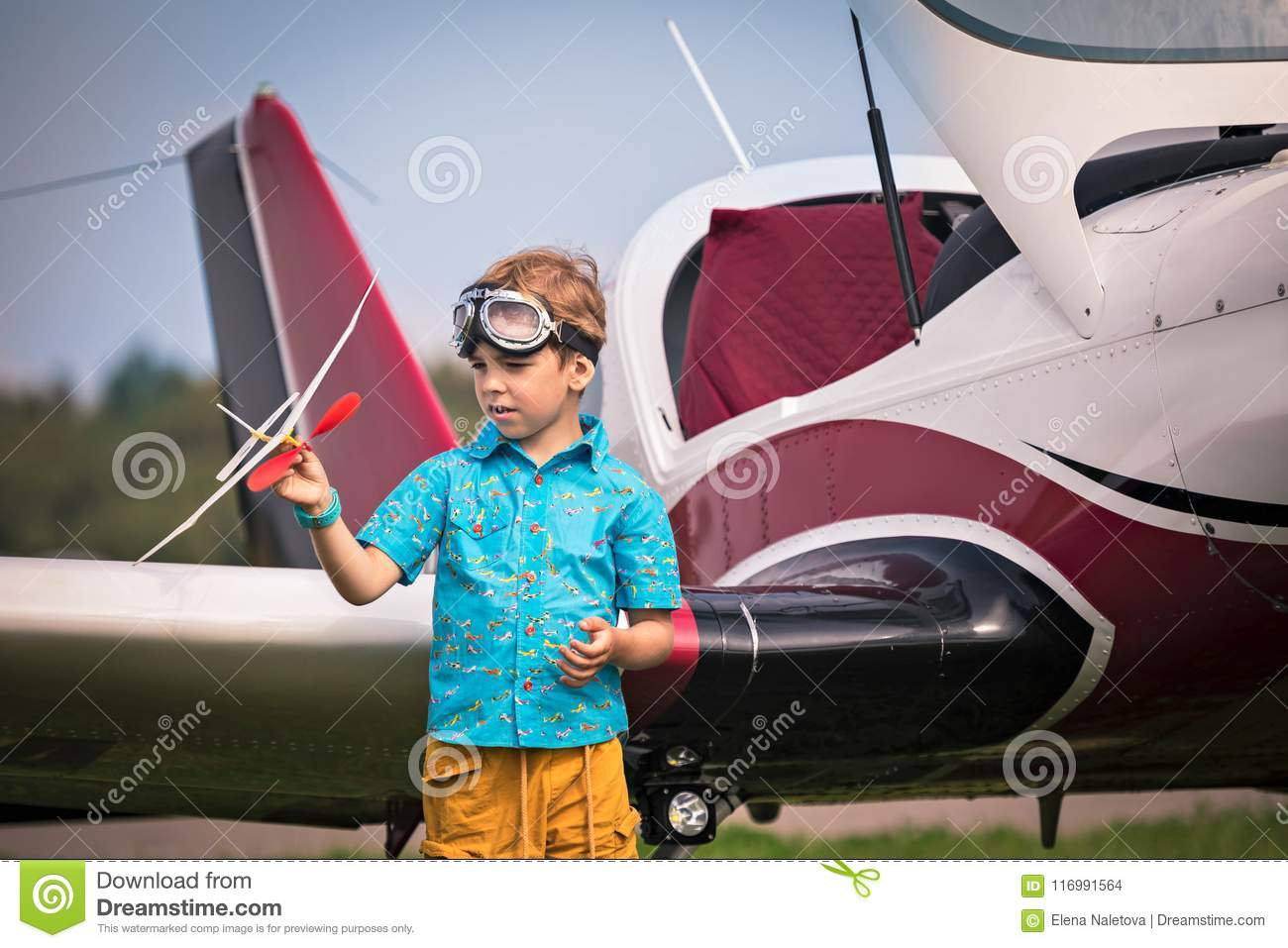 Caucasian boy in yellow shorts, a blue shirt and in aviation points holds the toy plane in hand and h