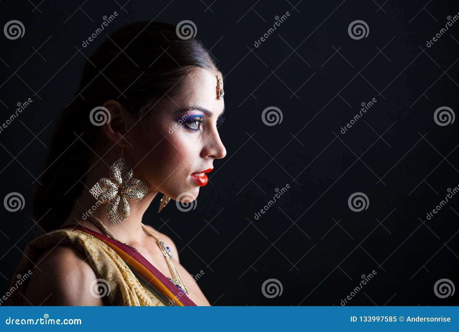 3f175db818 Caucasian brunette woman in brown indian national dress sari in dark studio  background