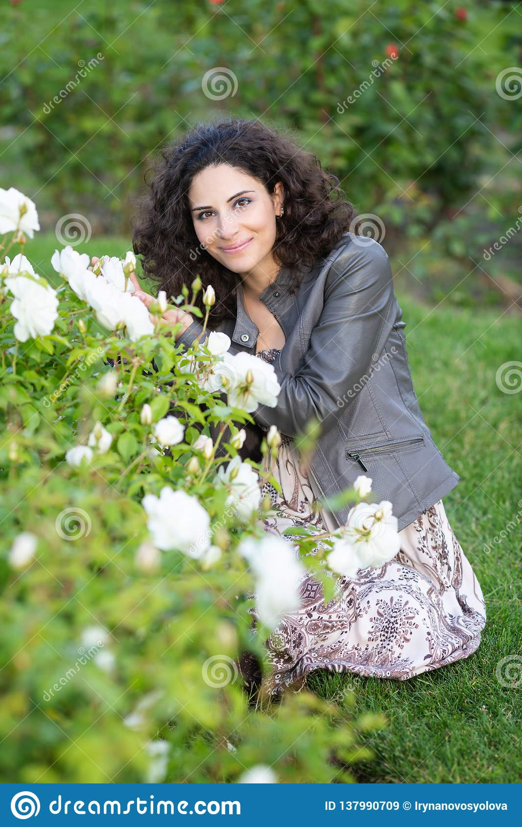 Caucasian brunette young woman sitting on green grass in a rose garden near yellow roses bush, smiling with teeth, looking to the